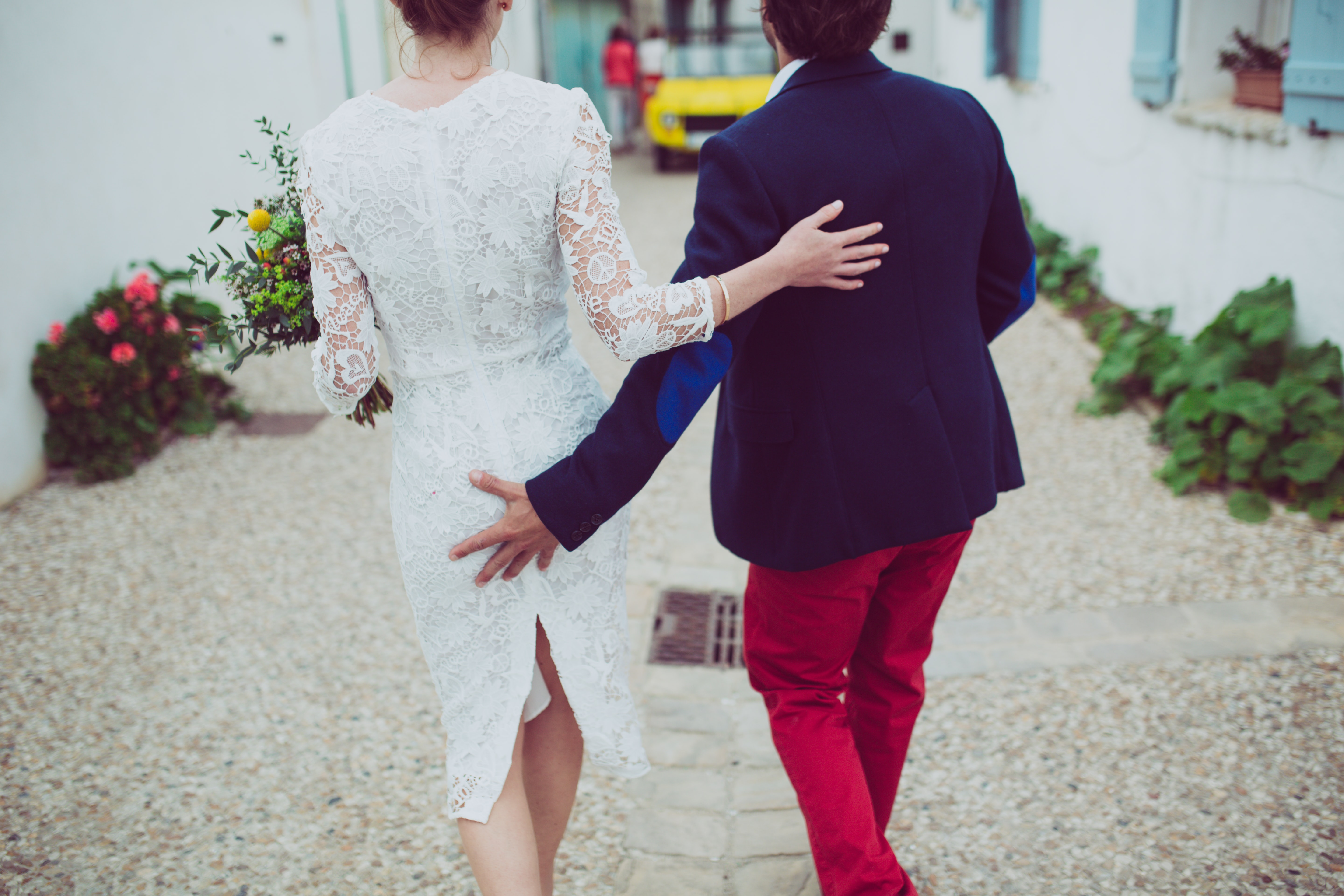 Man and woman are just married, walking away from the camera down an alley