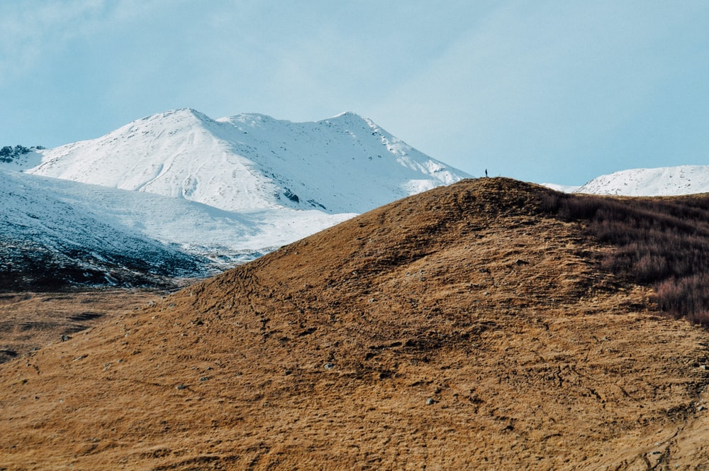brown mountain near mountain covered with snow