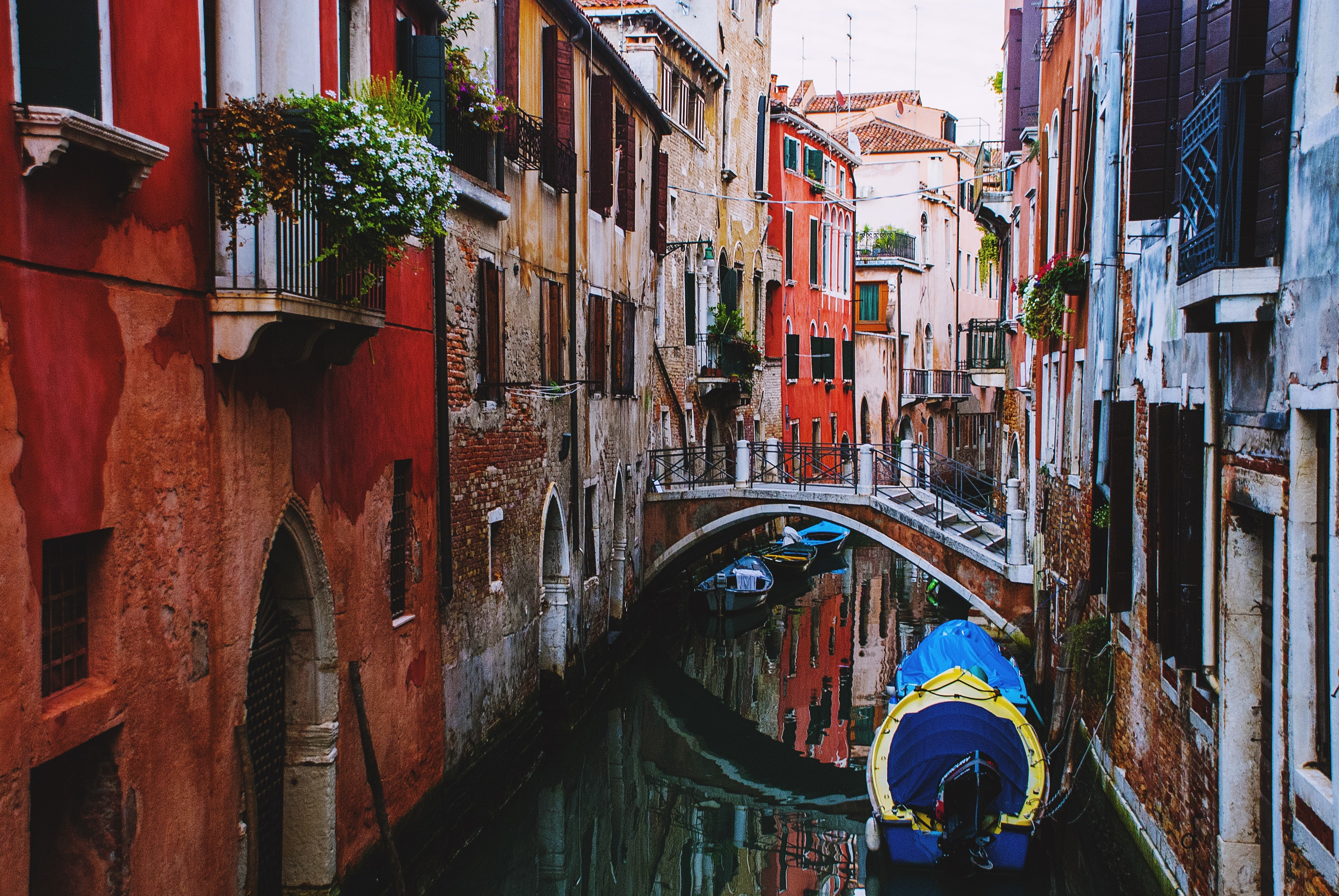 A canal with a bridge between red brick buildings in Venice