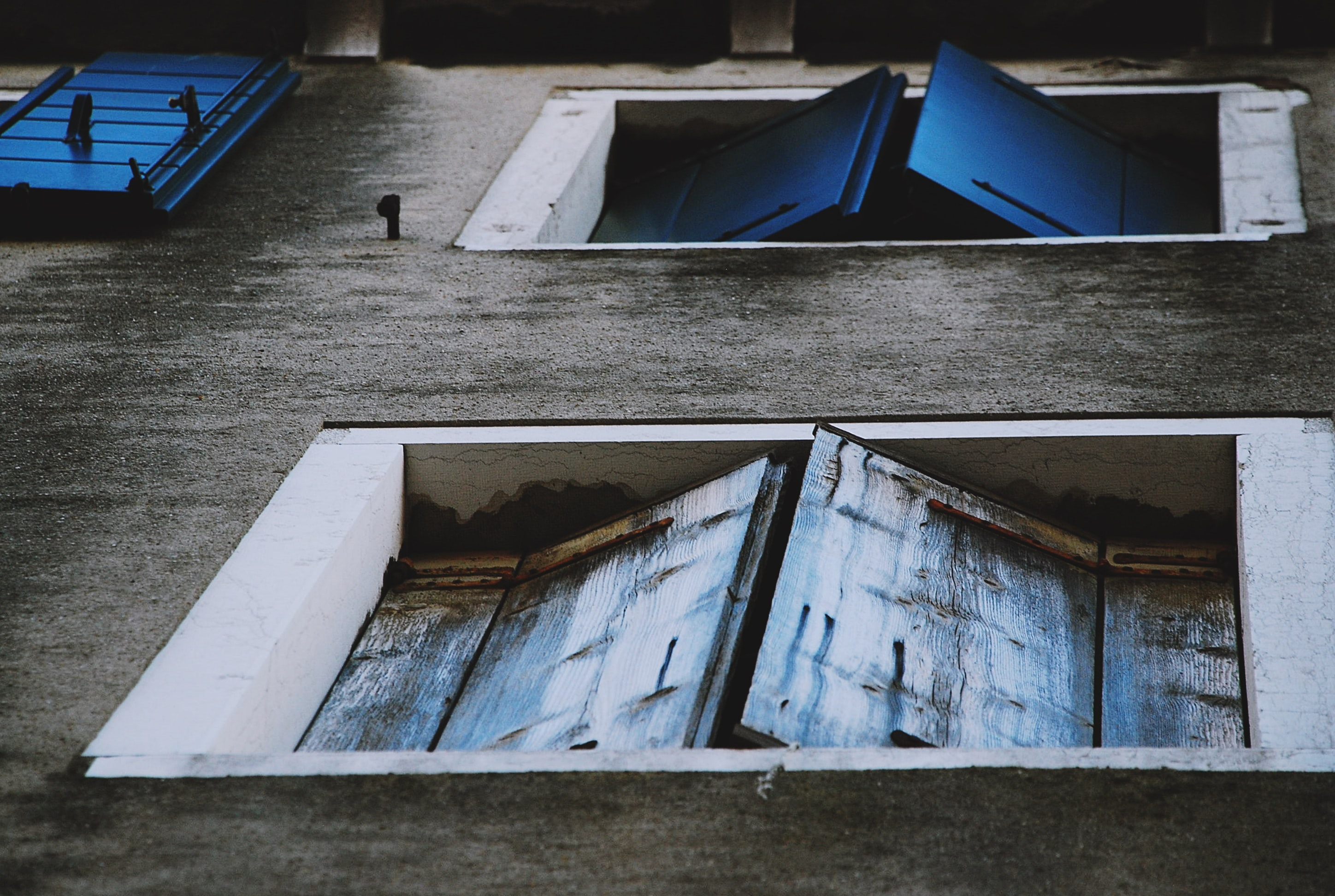Worn blue window shutters from below with grey wall and white frame, Metropolitan City of Venice
