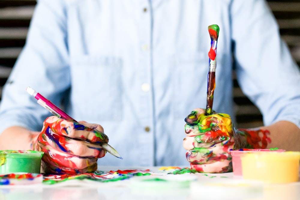 Iowa man sits at a messy table while holding paint covered pencil and brush