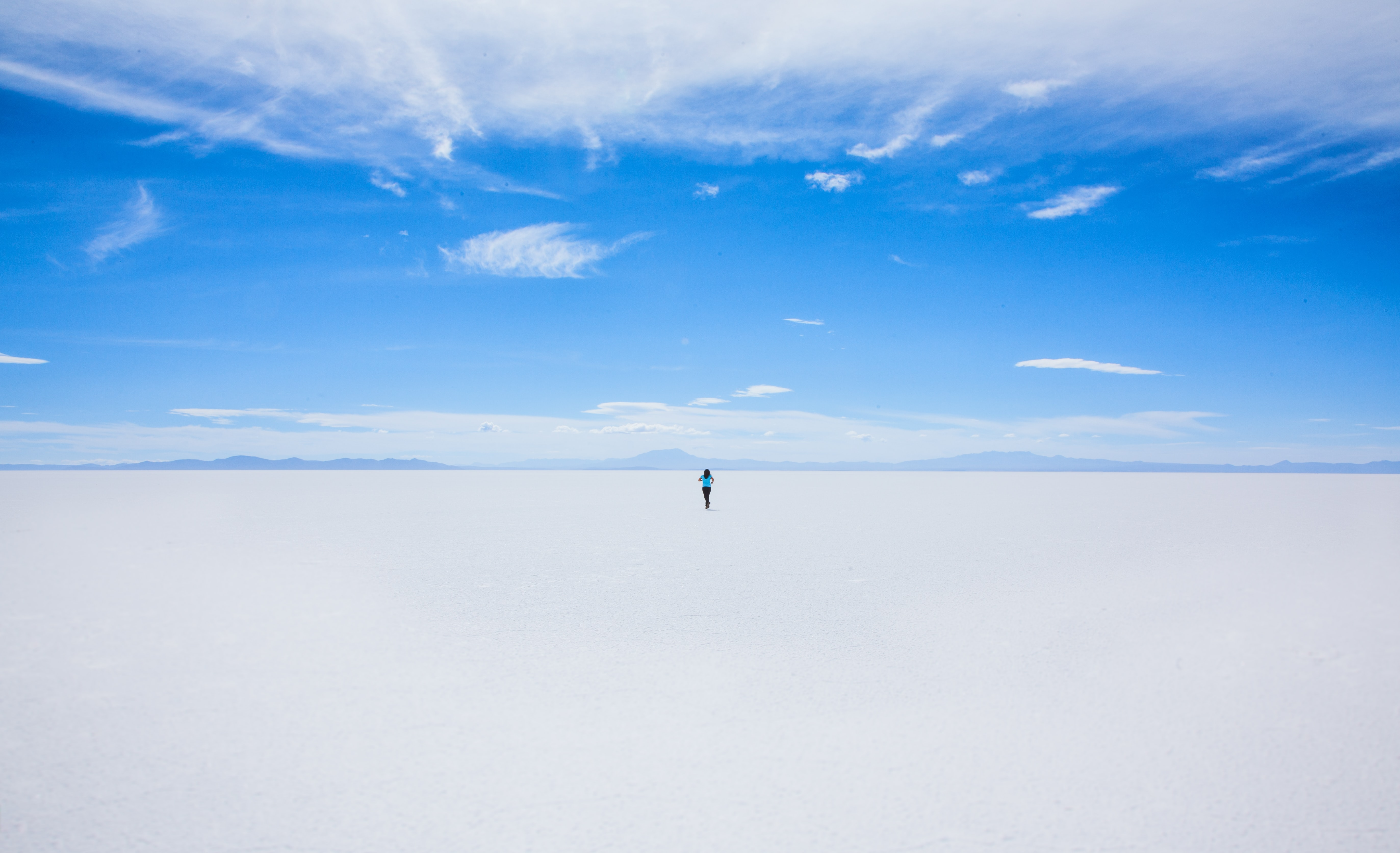 Hiker walks alone toward the desert horizon in Uyuni Salt Flat