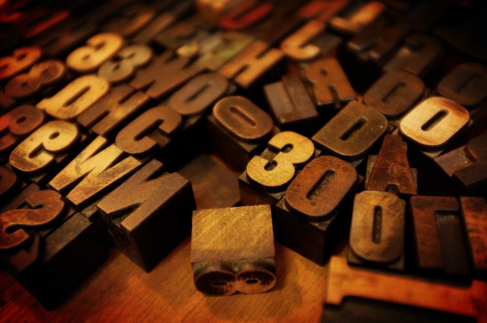 tilt shift lens photography close shot of brown letter and number blocks