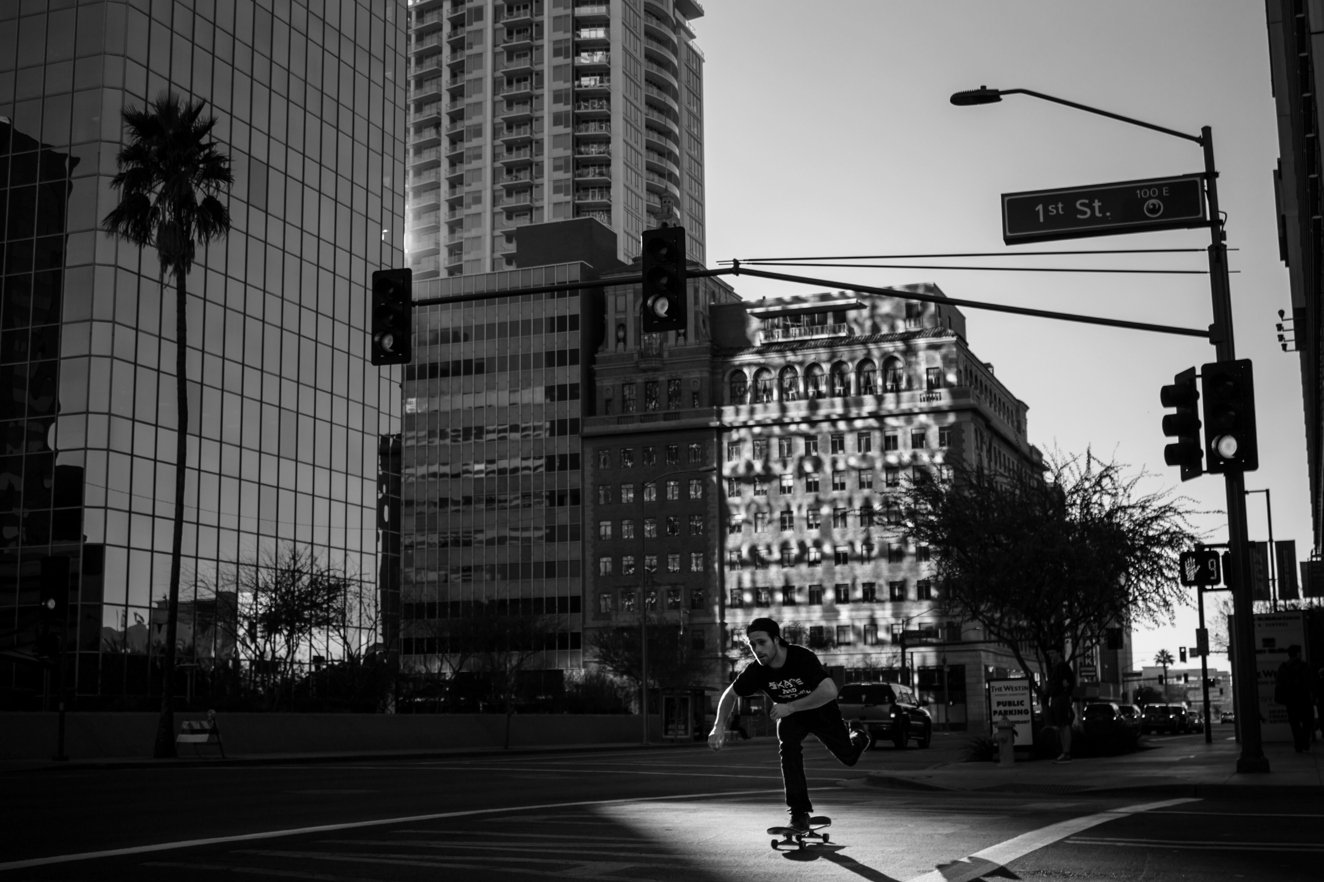Black and white shot of young man skateboarding down city centre street in Phoenix