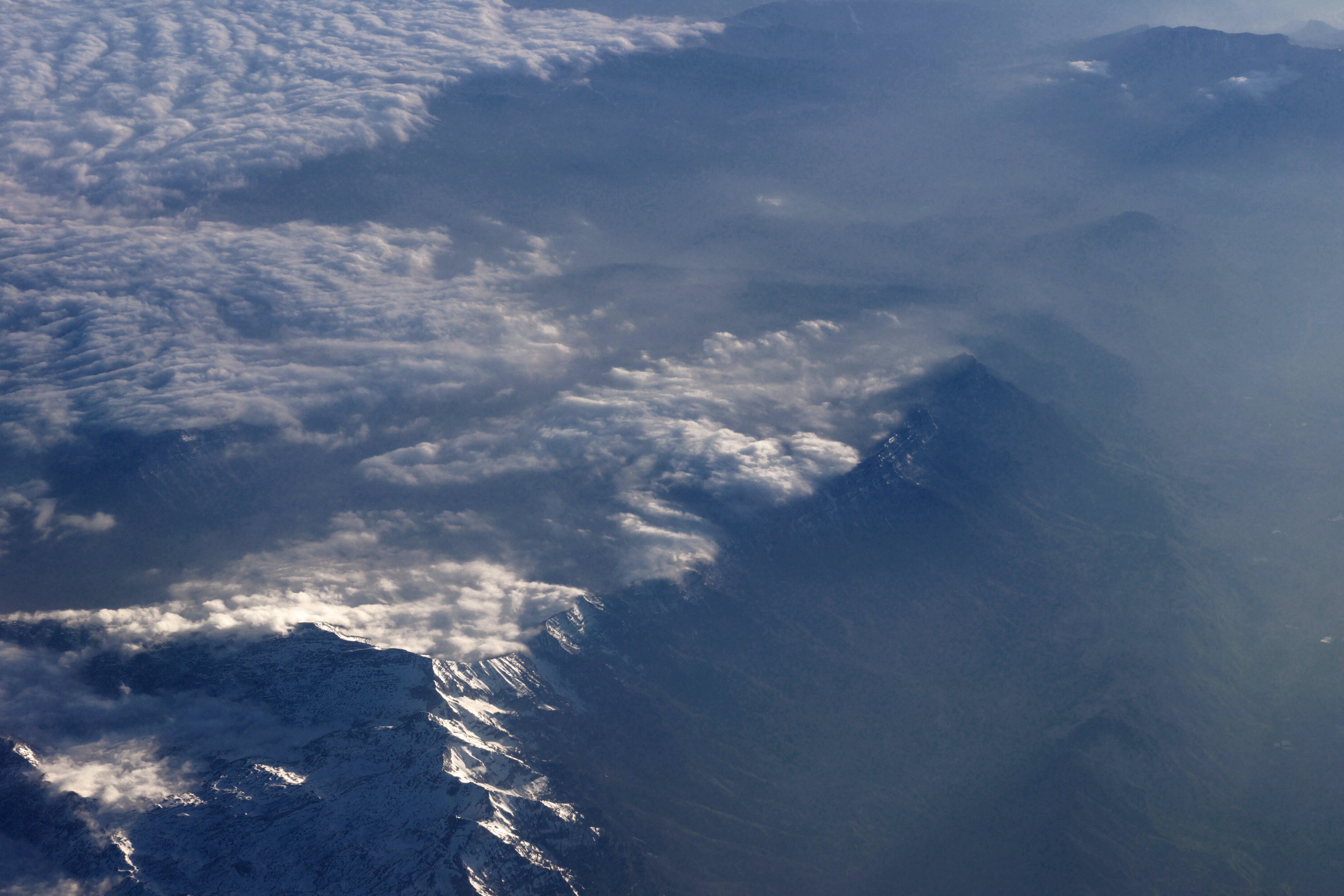 Aerial view of the peaks of a mountain range and clouds from above