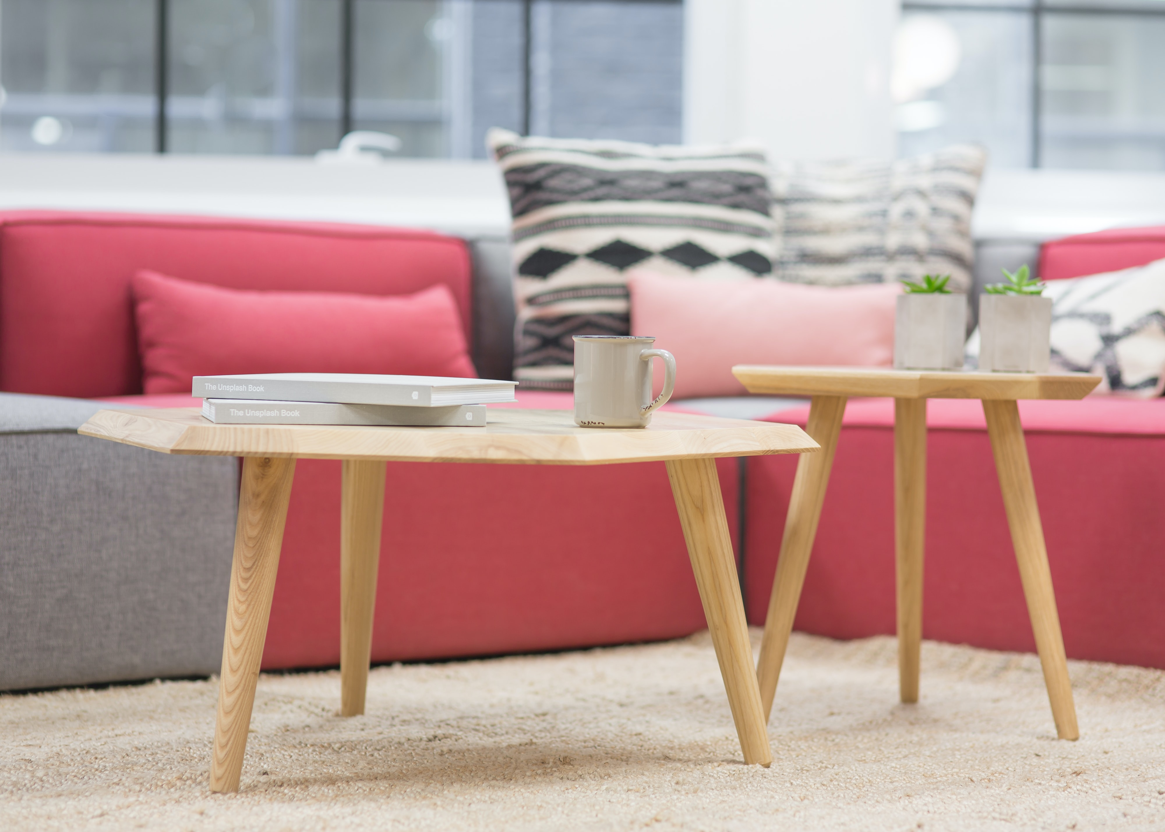 Coffee tables with potted plants, two books and a mug near a grey and pink sofa