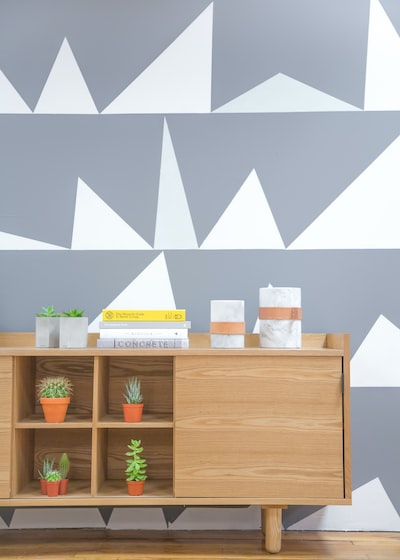 a,desk,with,pot,green,plant,and,a,stack,of,book,near,a,wall,with,a,geometr,pattern