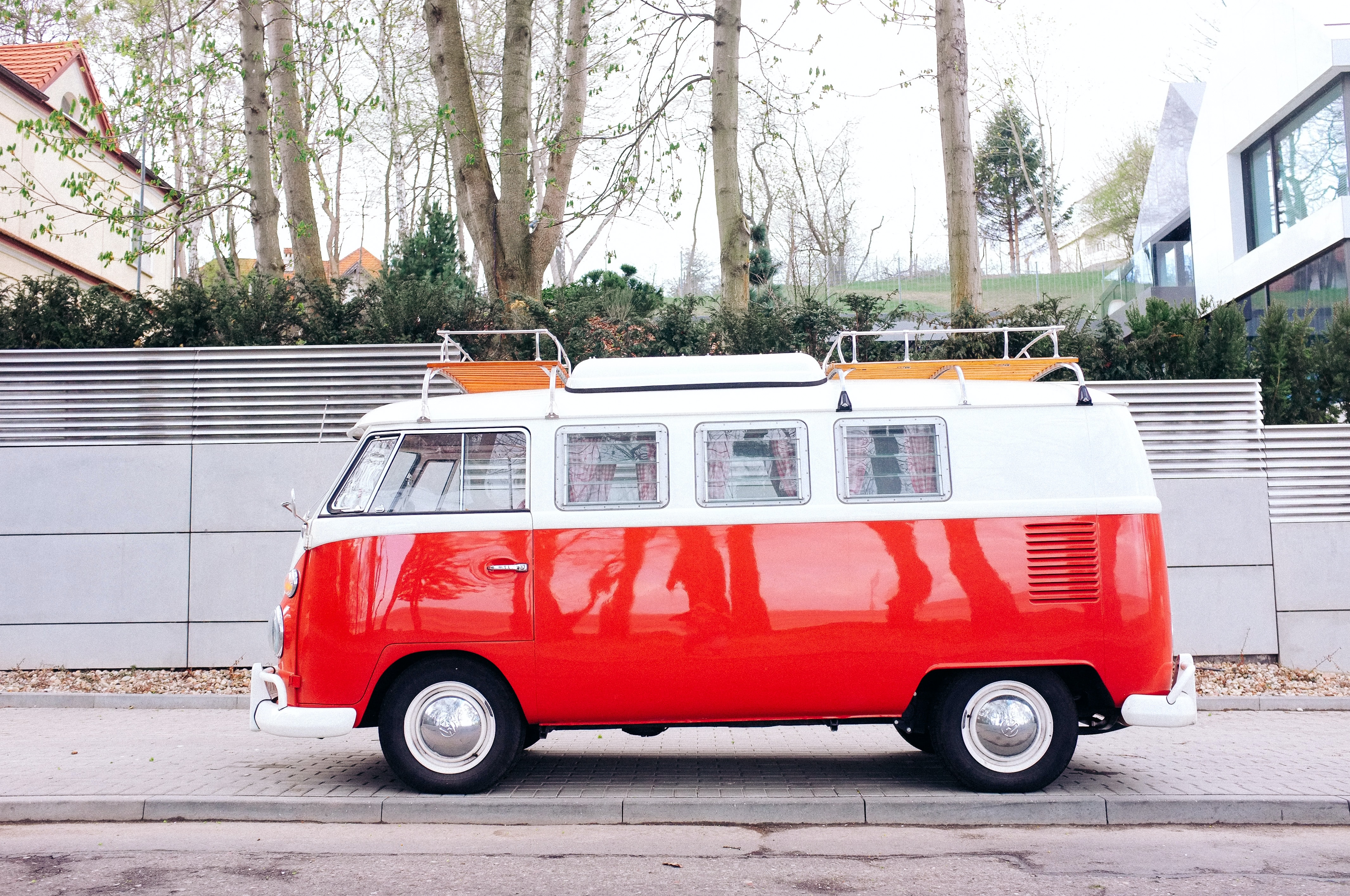 A red-and-white vintage minibus parked on the sidewalk