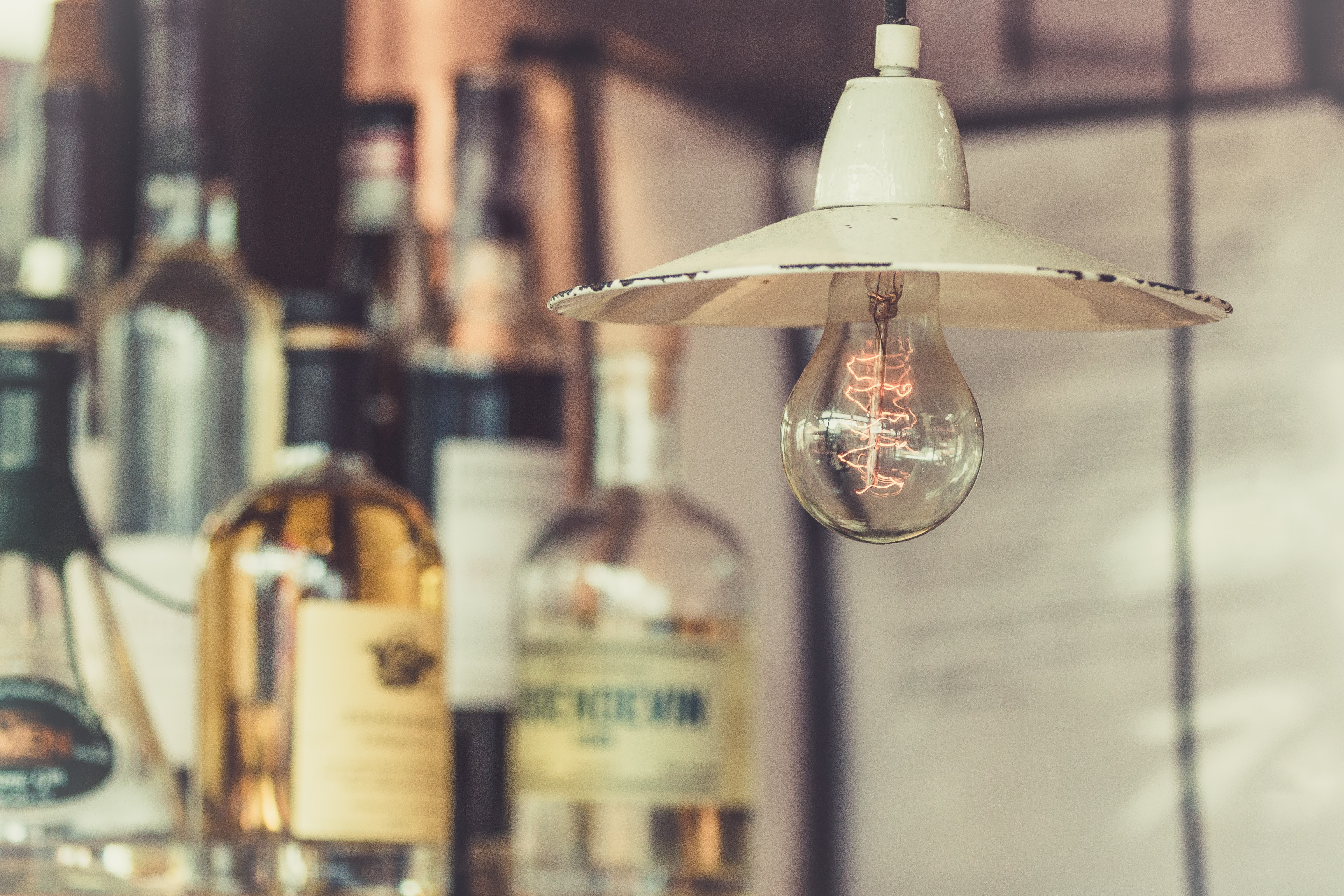 A macro view of a light bulb under a light pendant with alcohol behind it in Torvehallerne