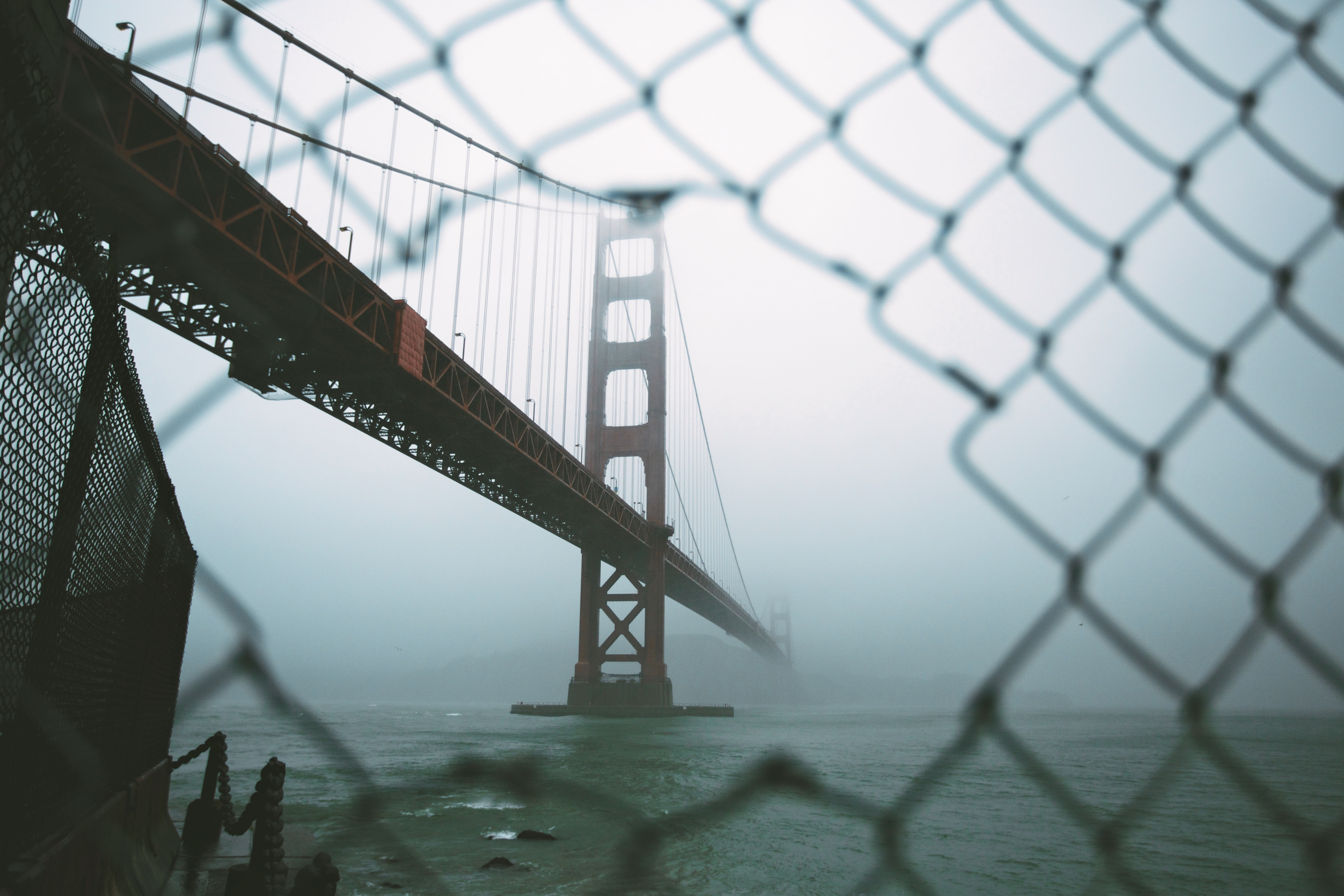 Aerial view from a chainlink fence of the San Francisco golden gate bridge covered by fog