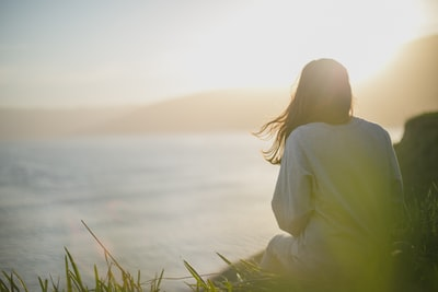 woman wearing gray long-sleeved shirt facing the sea