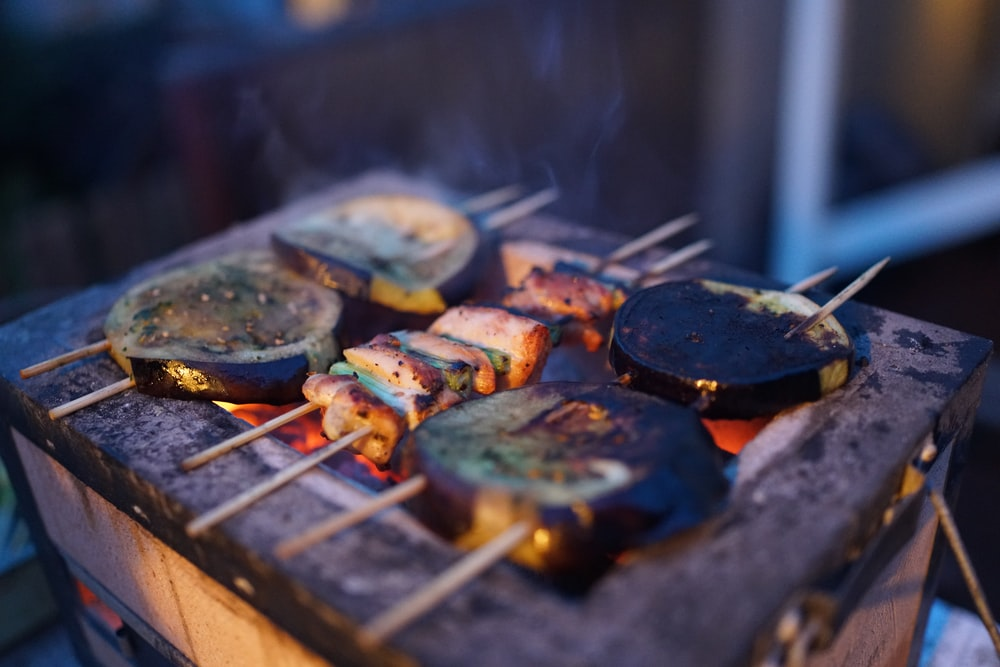 three assorted barbeques on black grill