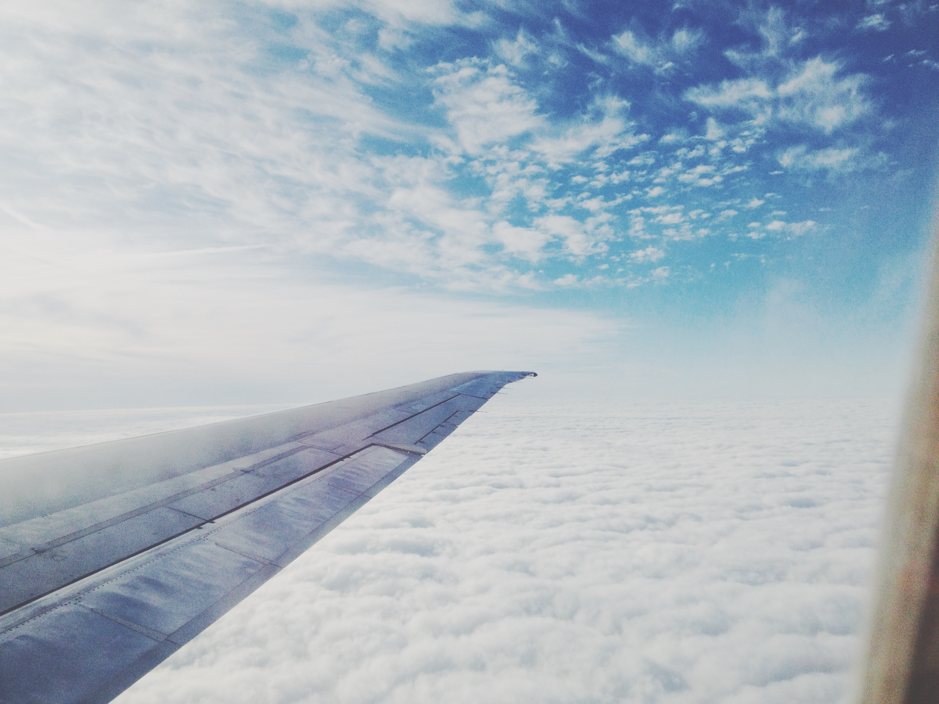 airplane wing soaring on white clouds