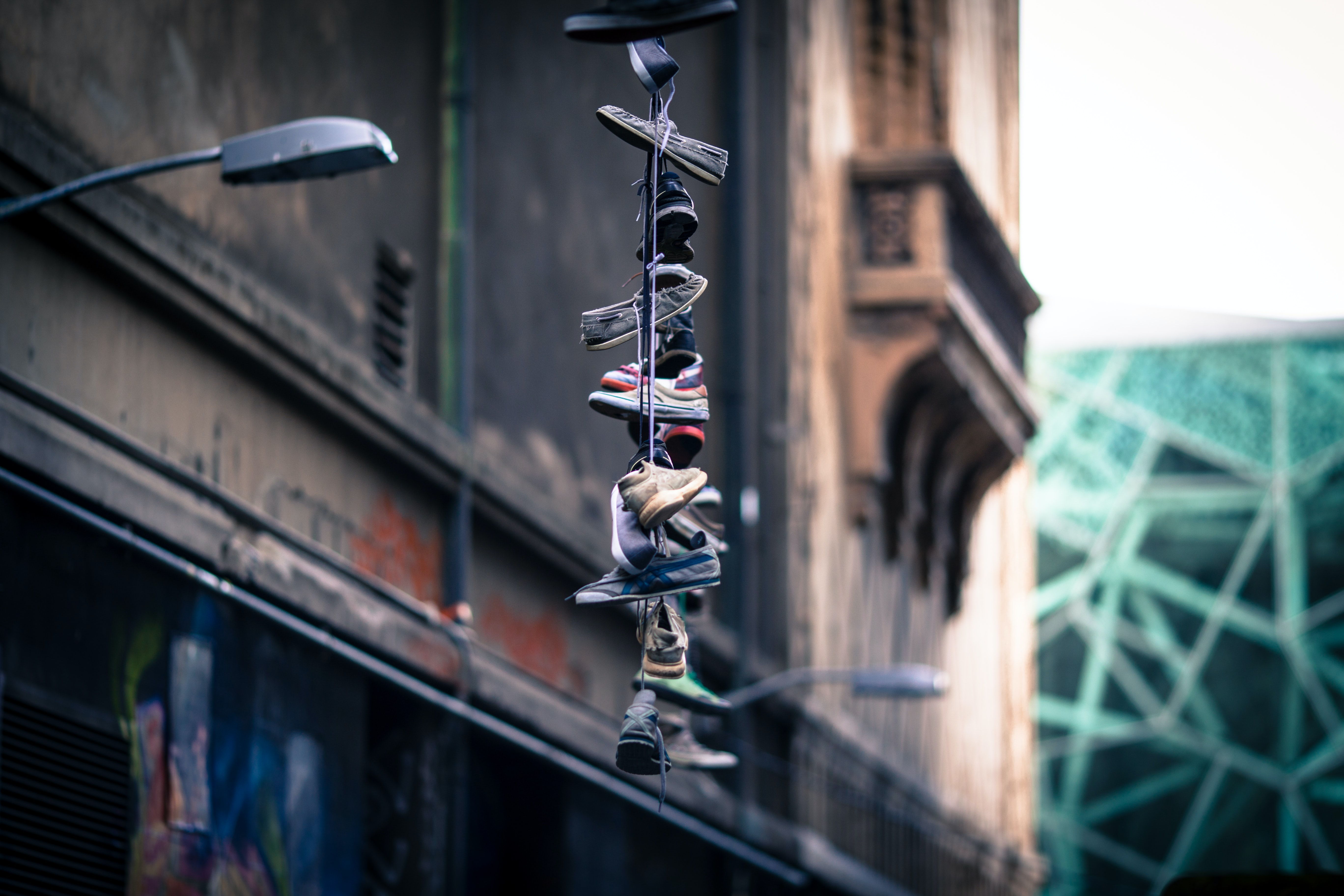 Multiple sneakers lace-tied together hanging from streetlight as tribute in decaying urban area, Hosier Lane