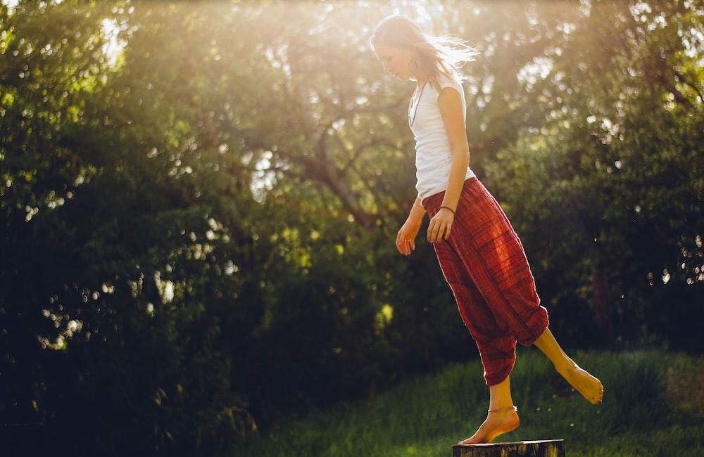 woman standing on wood log