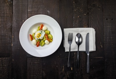 sunny side up egg, boiled quail eggs, sliced red tomatoes, and sliced green bell pepper inside round white ceramic plate in a fine dining set plate zoom background