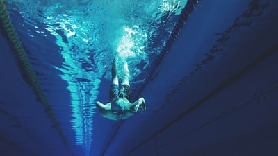 man swimming in swimming pool deep teams background