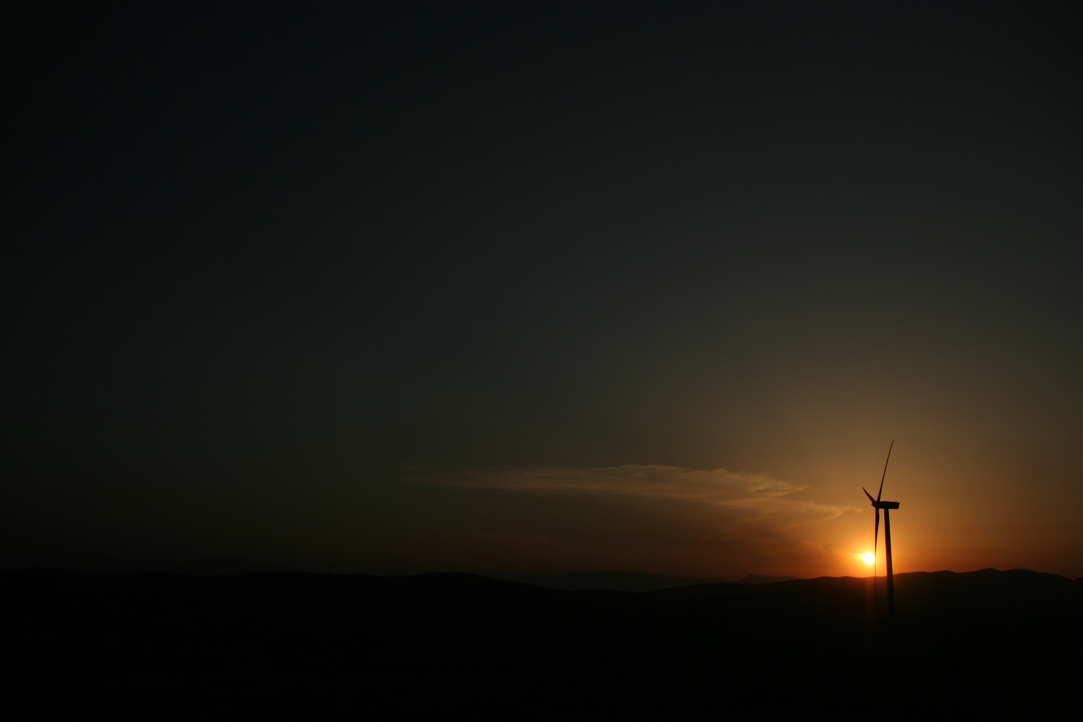 The sunset shines a bright light upon a Pikrolimni wind turbine standing in the darkness of the night