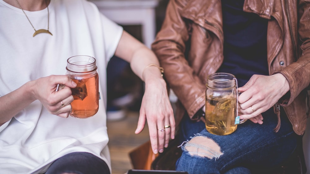 two person sitting while holding clear glass mason mugs