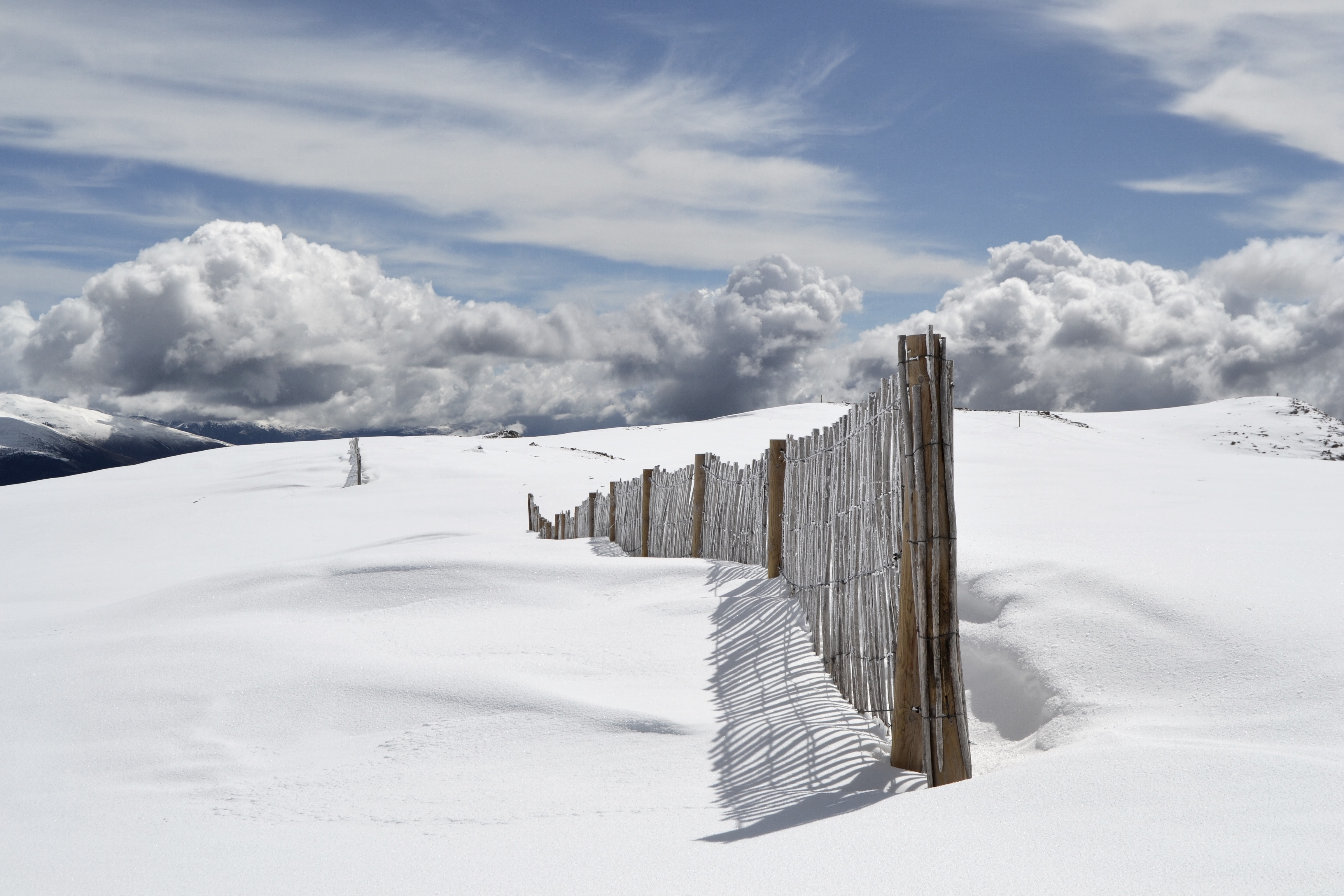 The end of a wooden fence traveling along a snow covered mountain