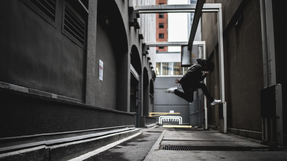 person wearing black pants and white shoes jumpshot
