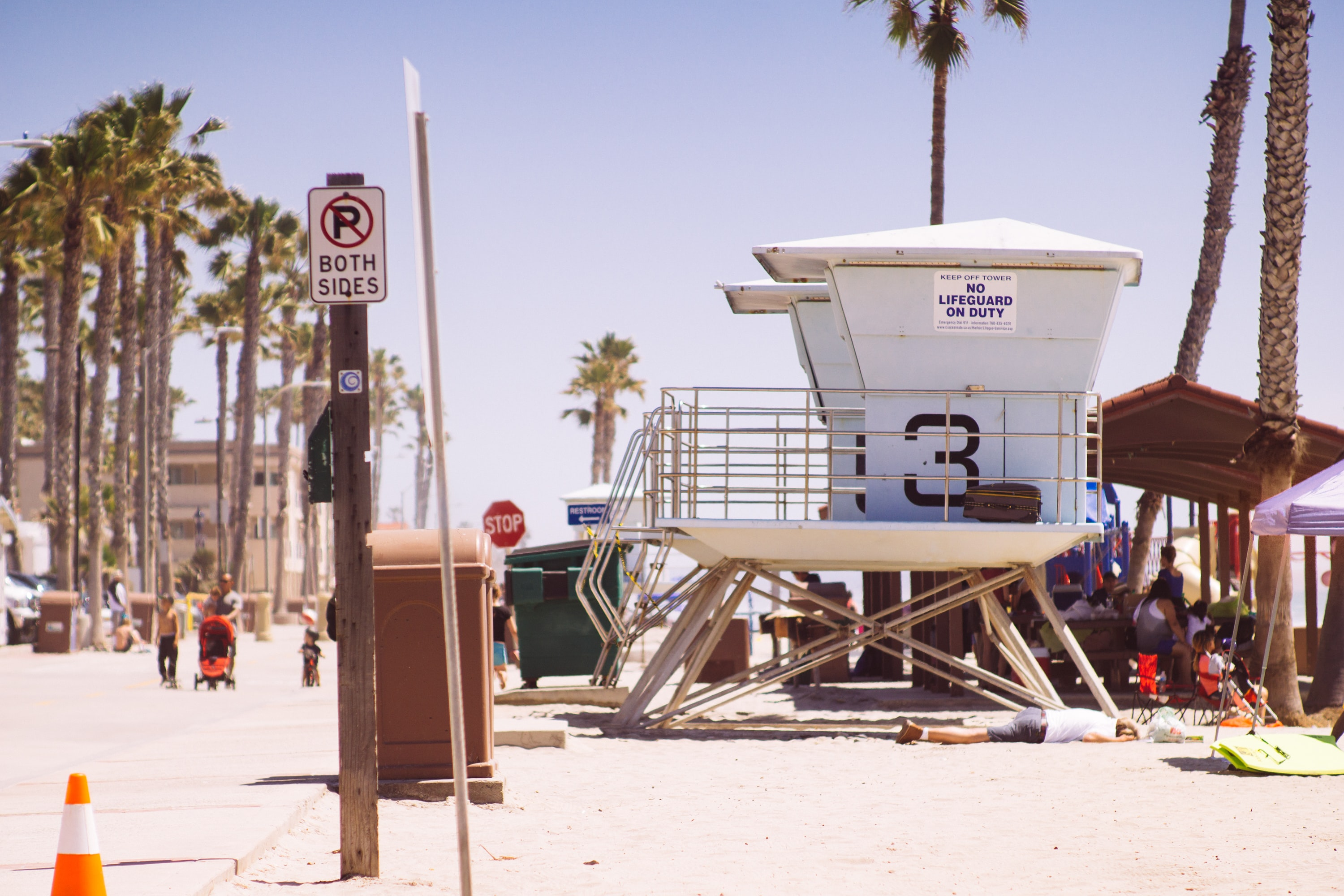 Beach premises featuring lifeguard hut, palm trees, a resting man and pedestrians  at Oceanside