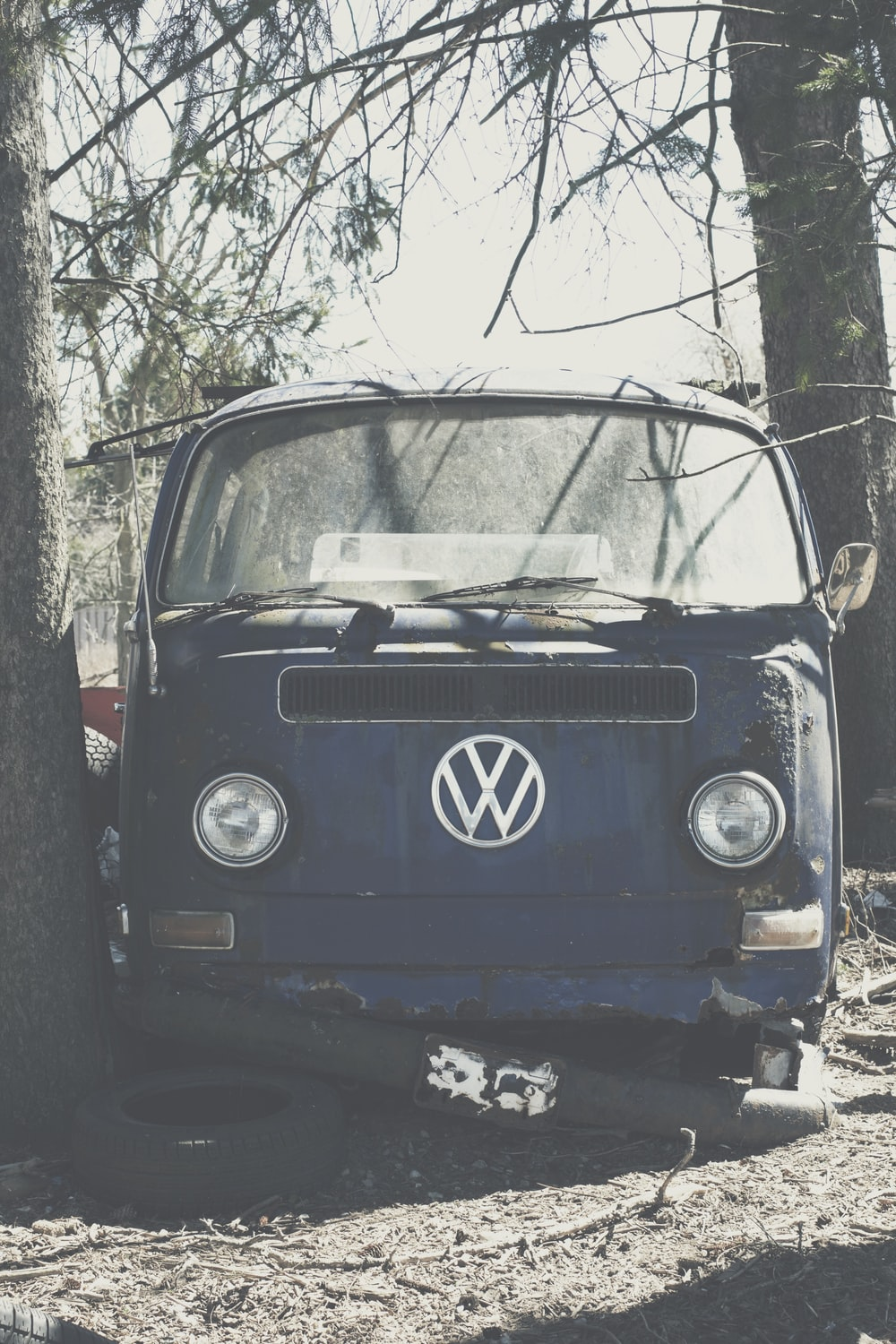 blue volkswagen t-2 parked beside bare tree during daytime