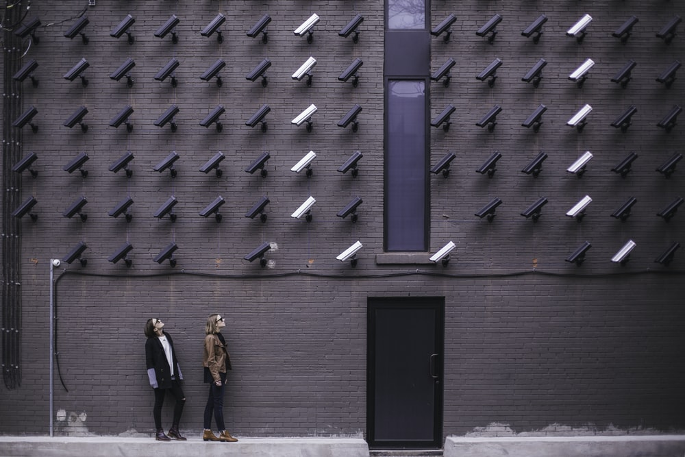 two women facing security camera above mounted on structure