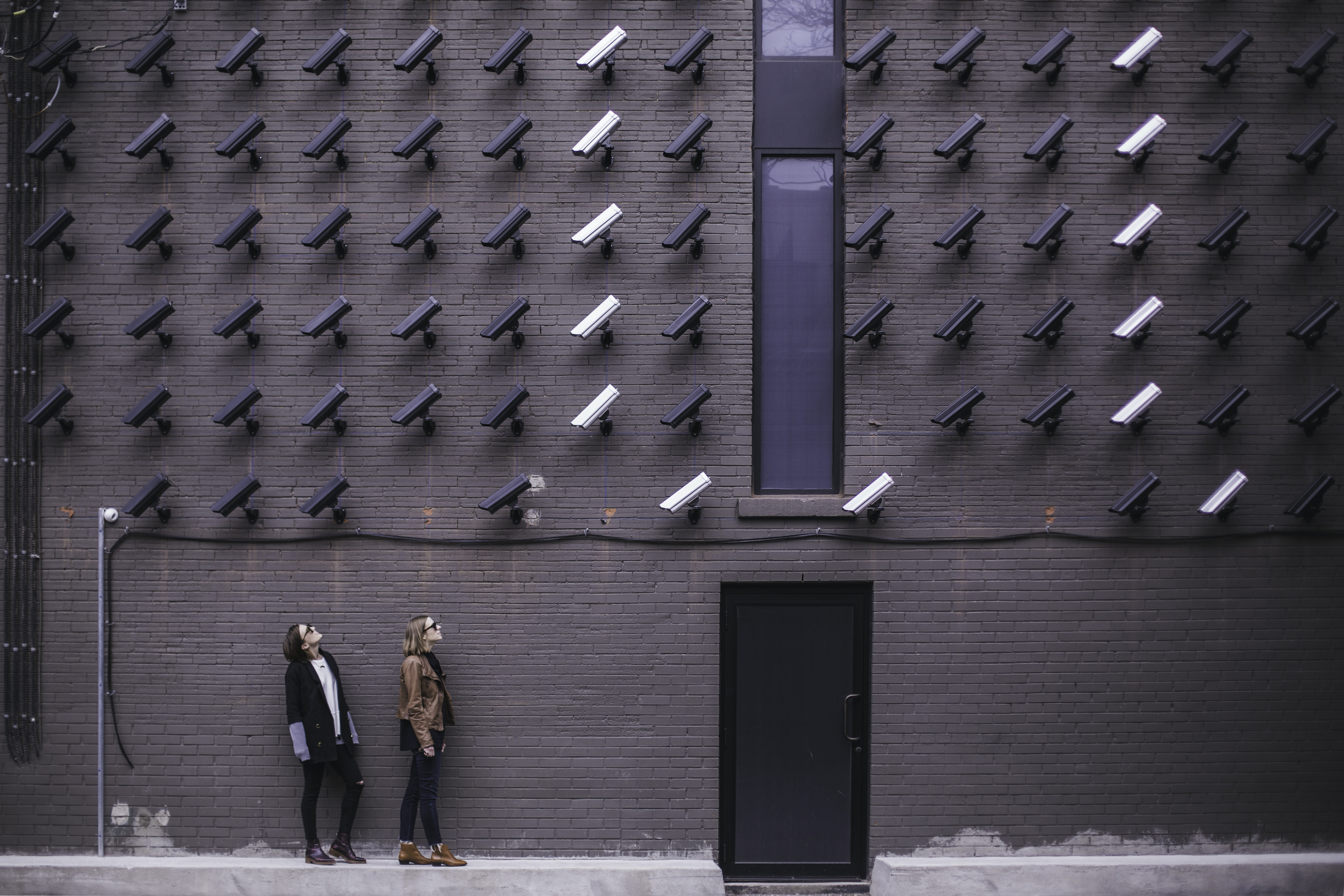 Women viewing modern art with black and white surveillance cameras on wall in Toronto