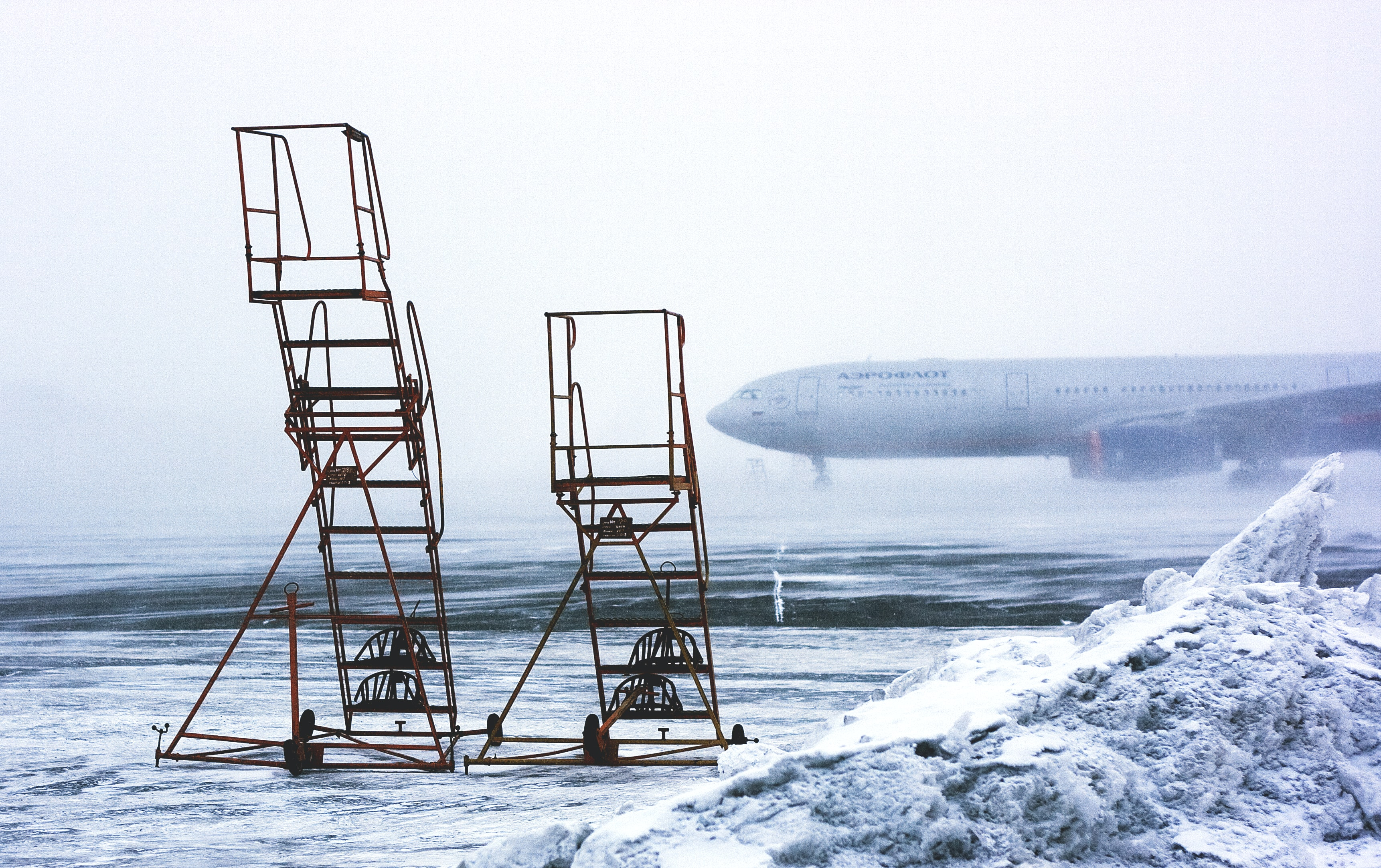 Two sets of airstairs sit next to each other on a frozen tarmac; a grounded plane is visible in the background