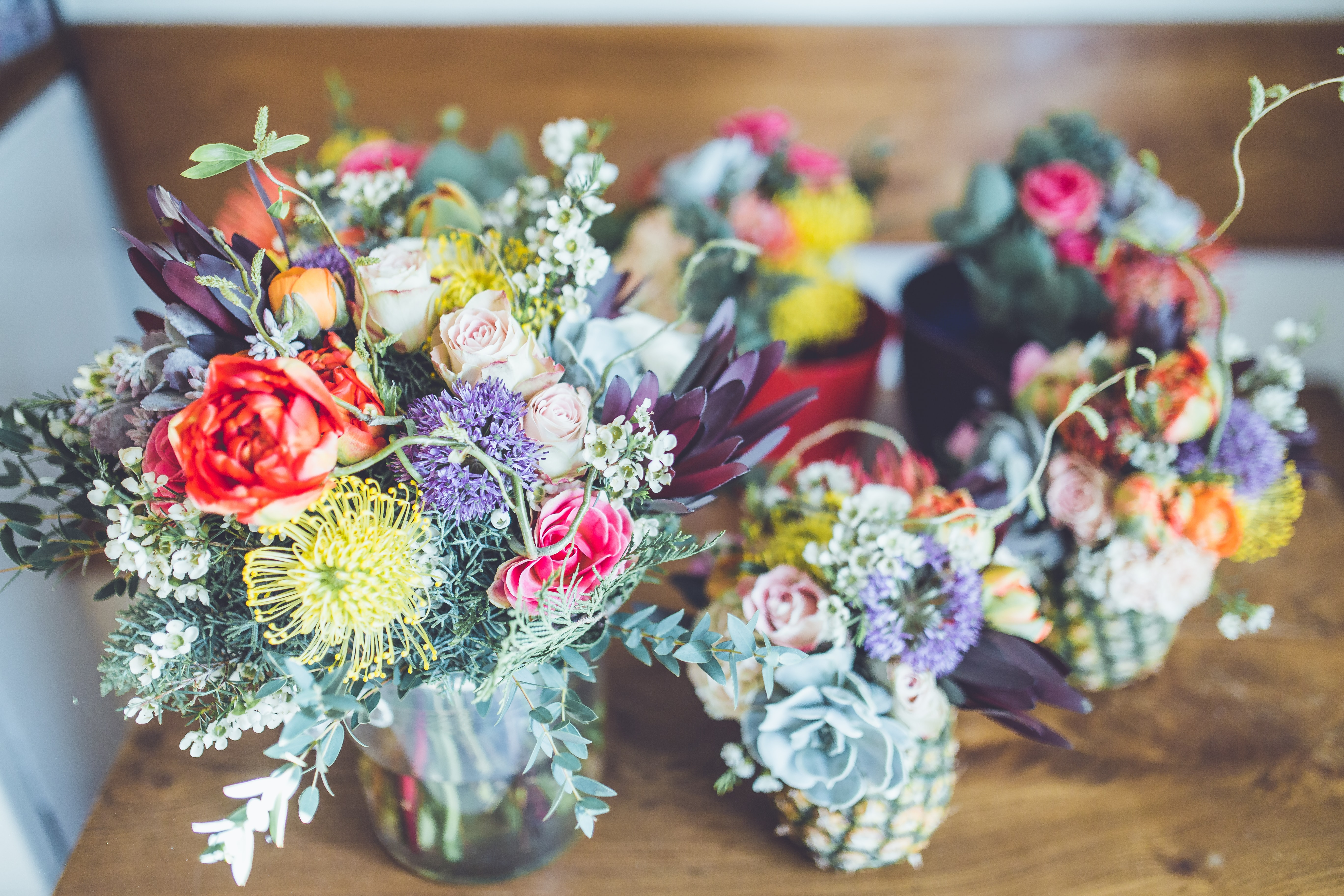 An arrangement of several floral bouquets with colorful flowers in small vases and pots