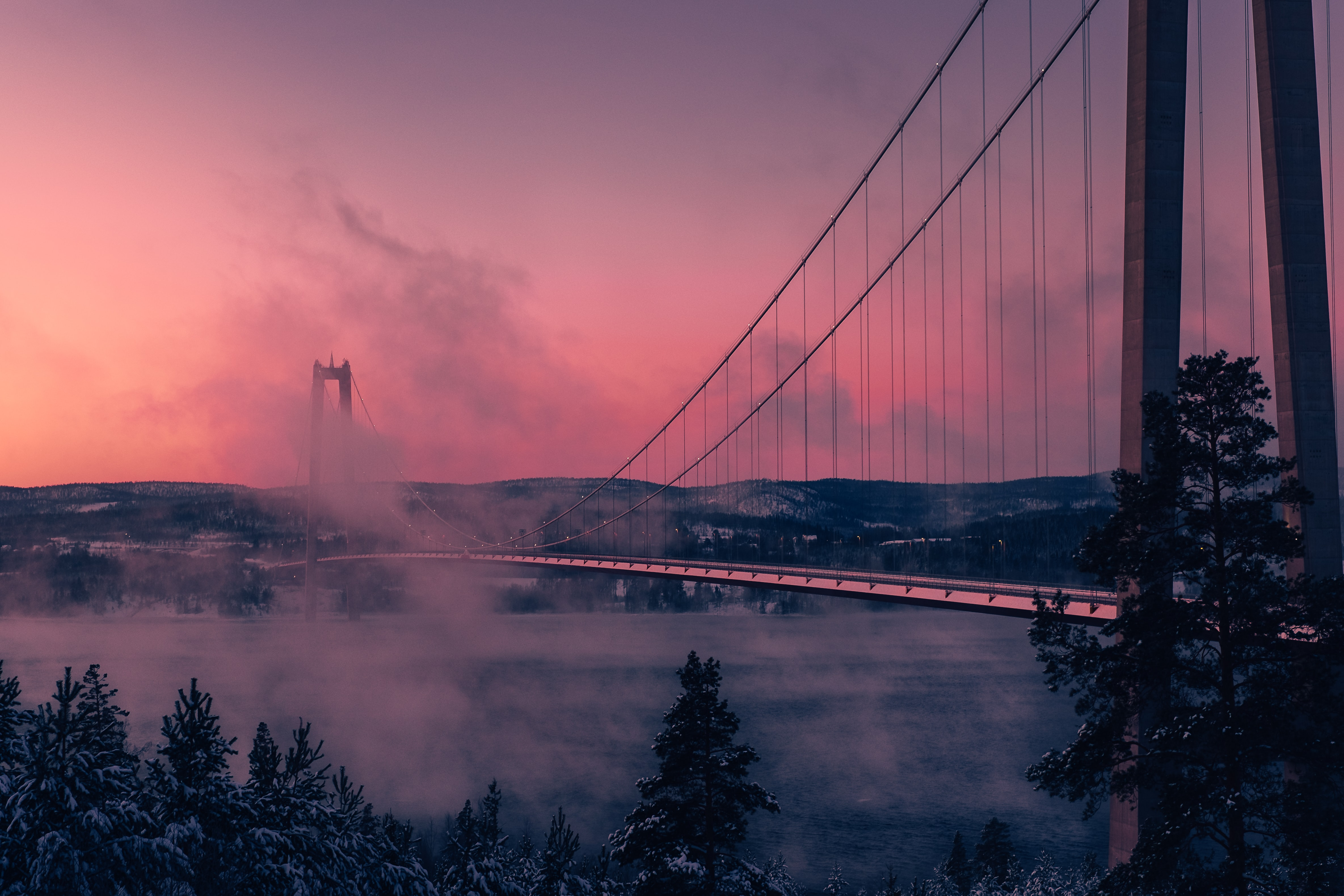 Clouds cover the Högakustenbron suspension bridge as a pink sunset covers the sky