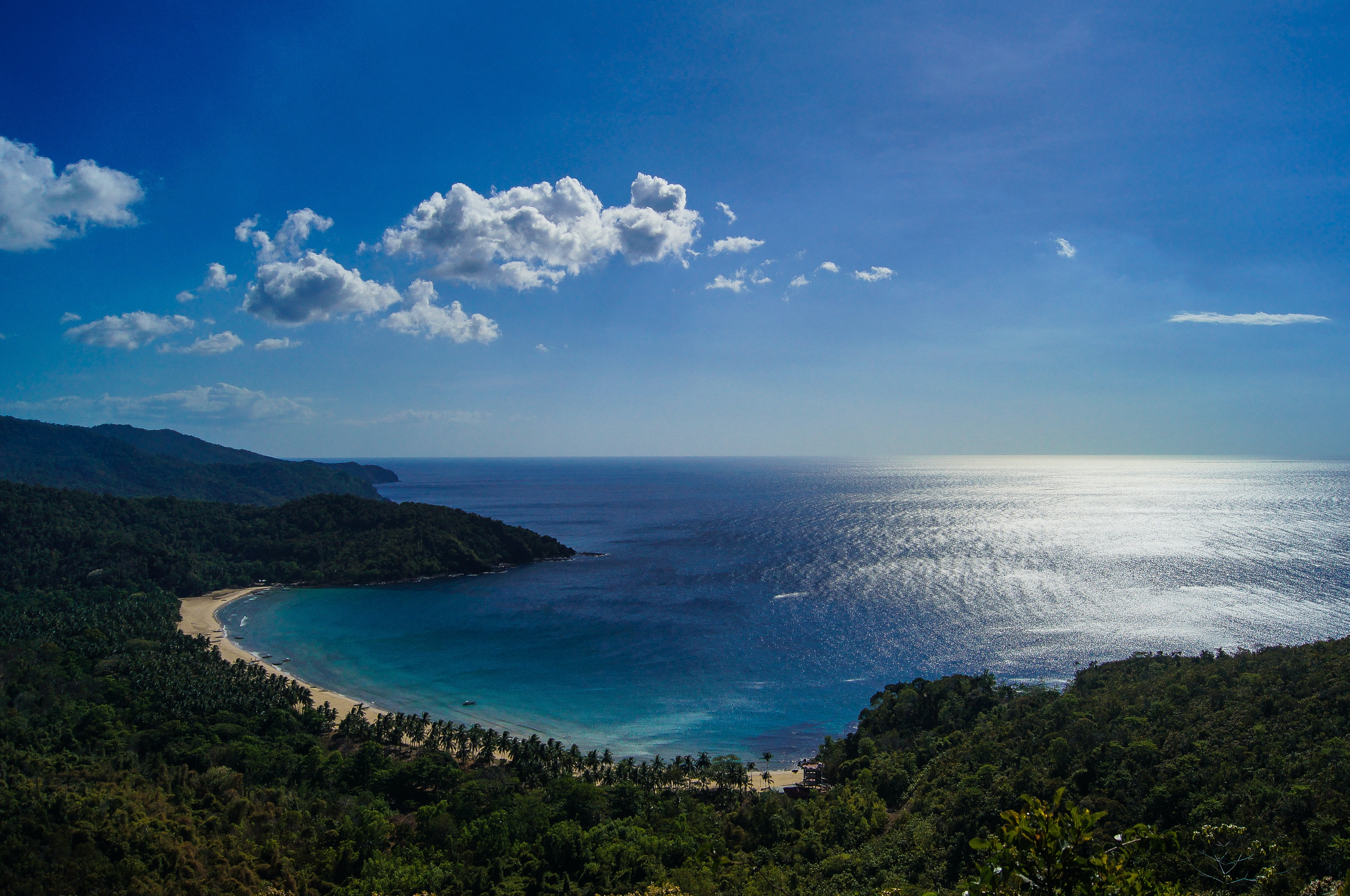 Impressive horizon featuring blue ocean, shore and clouds in the sky at a beach location