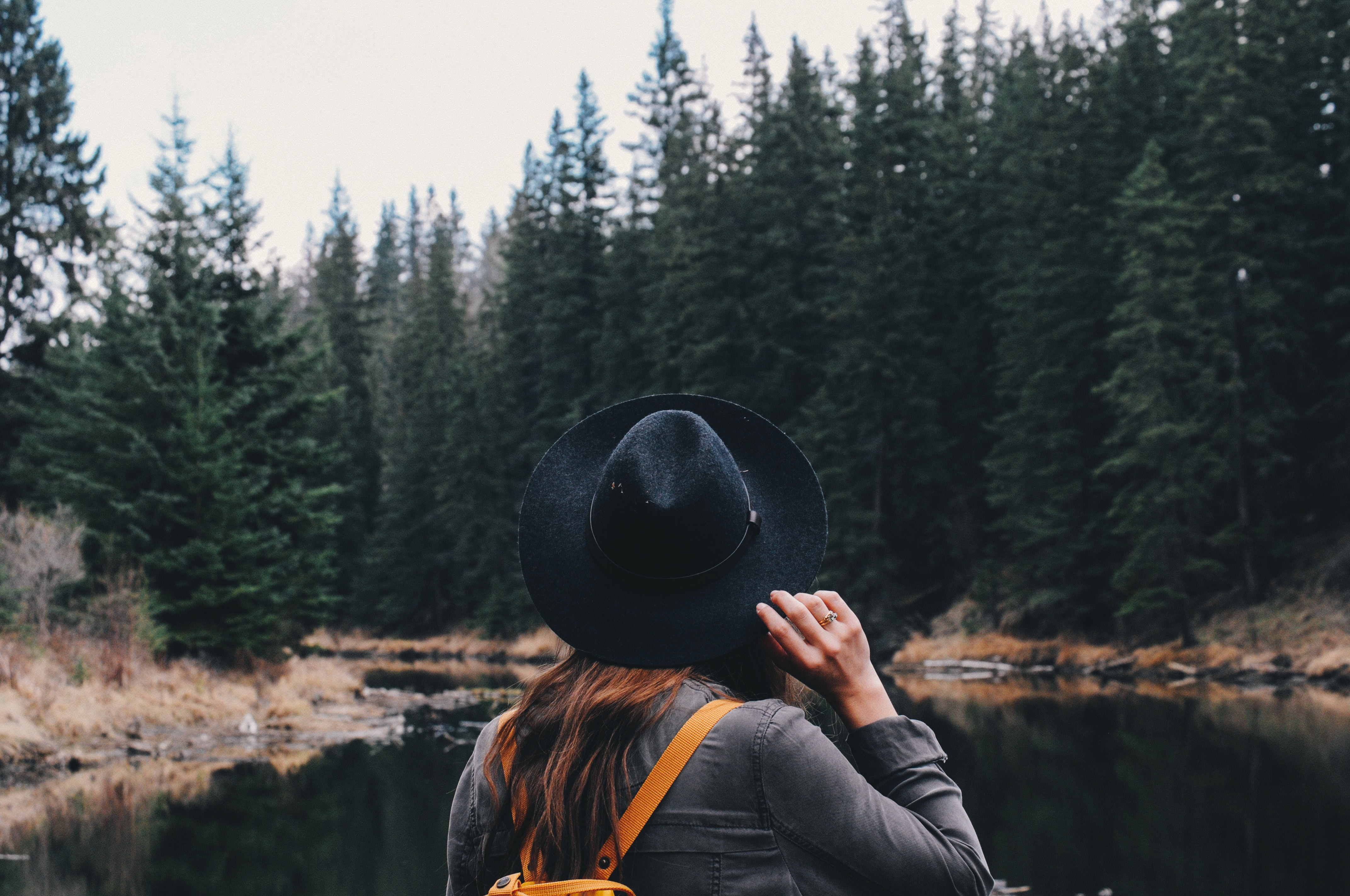 woman holding her hat while standing in front of river beside forests