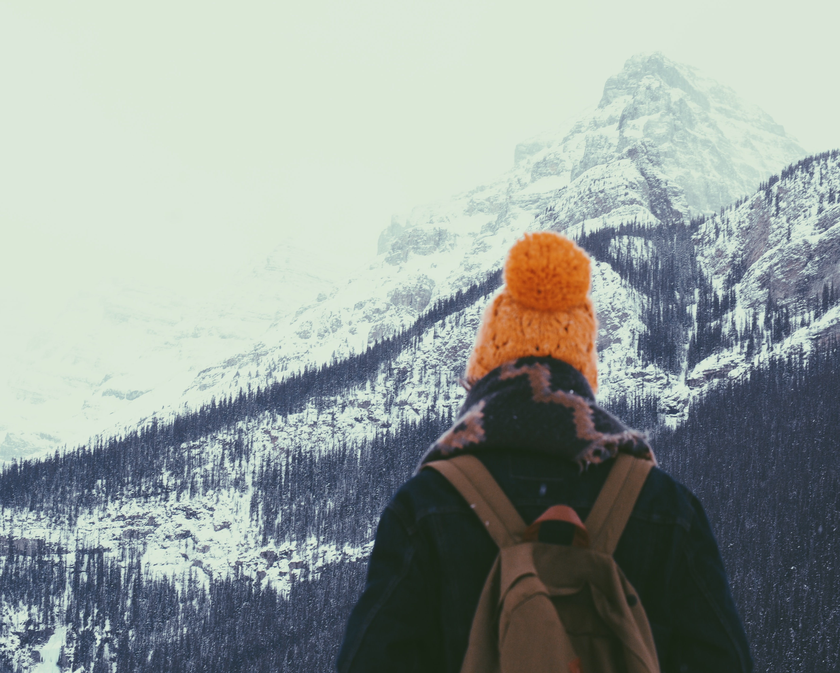 A person wearing a knit hat, big scarf, denim jacket, and brown backpack looking out at Lake Louise on a snowy winter day