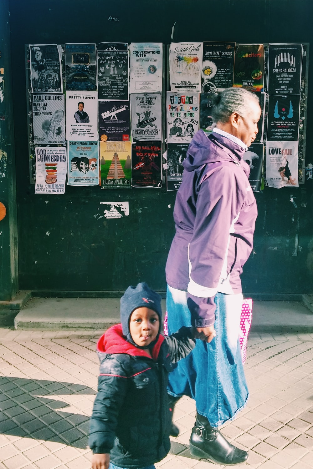 woman standing beside toddler