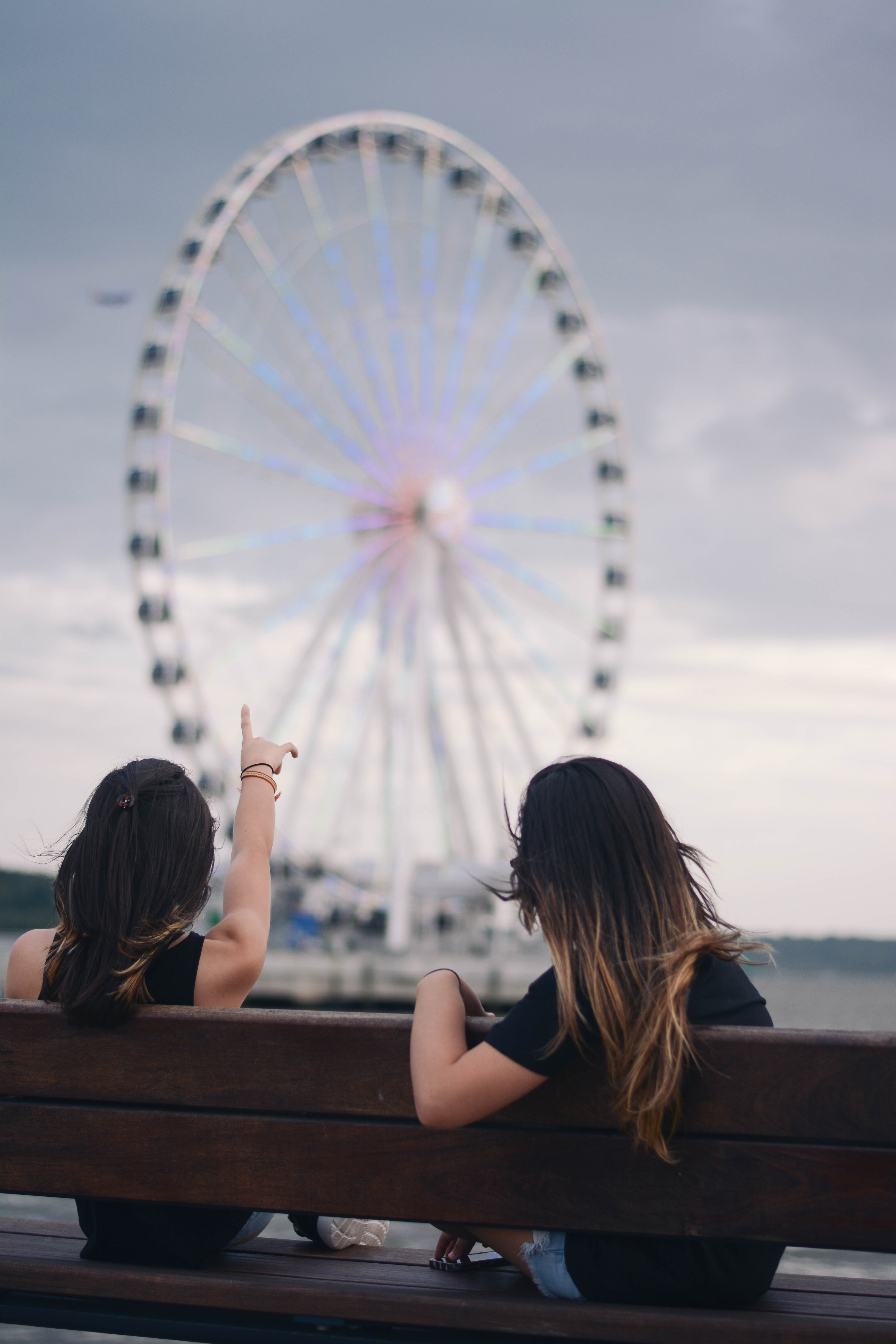 Women sitting on wooden bench looking and pointing at the National Harbor Ferris Wheel