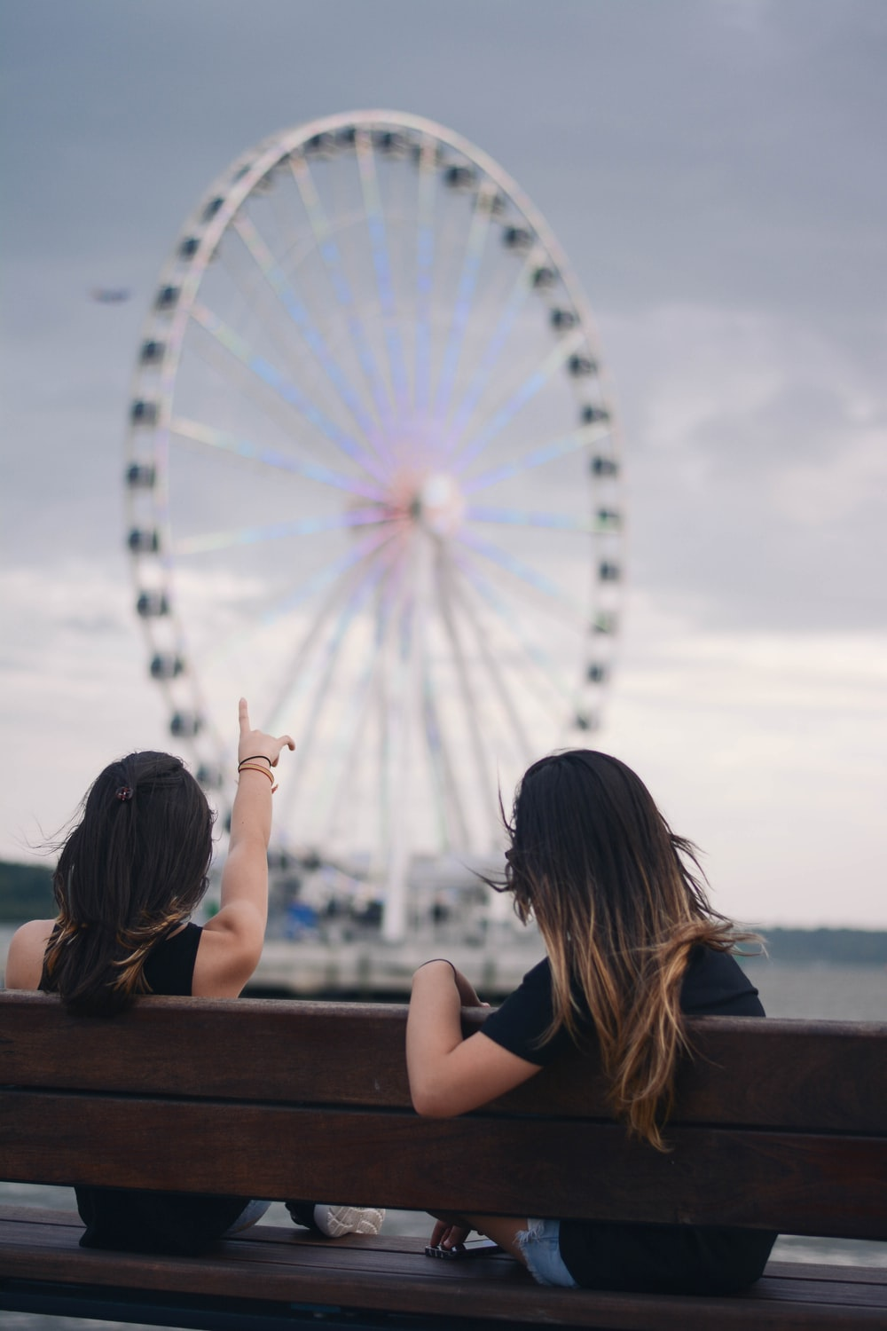 two women sitting on bench pointing white and blue Ferris wheel