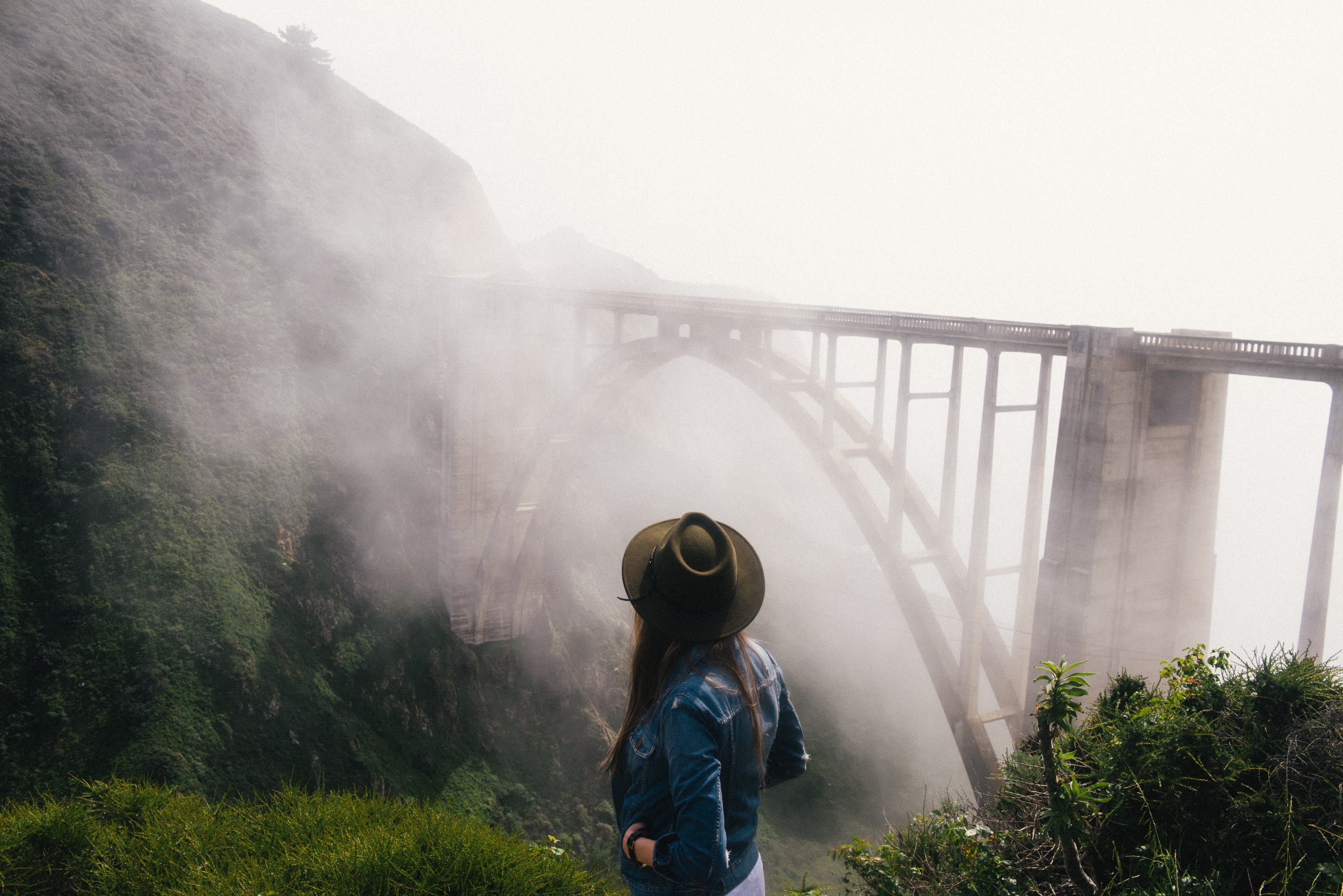 woman looking at gray concrete bridge with fogh