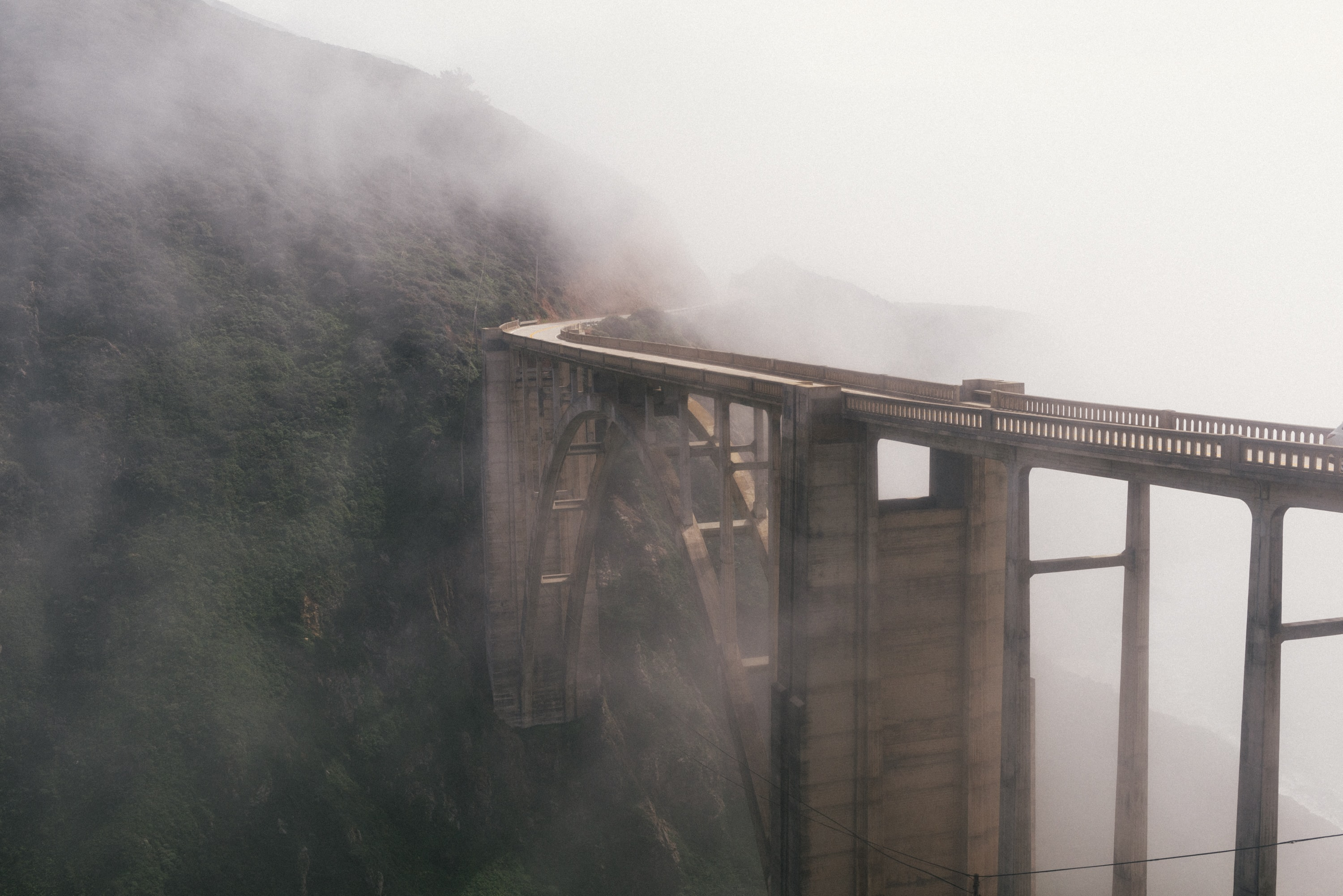 mist and gray bridge near mountain