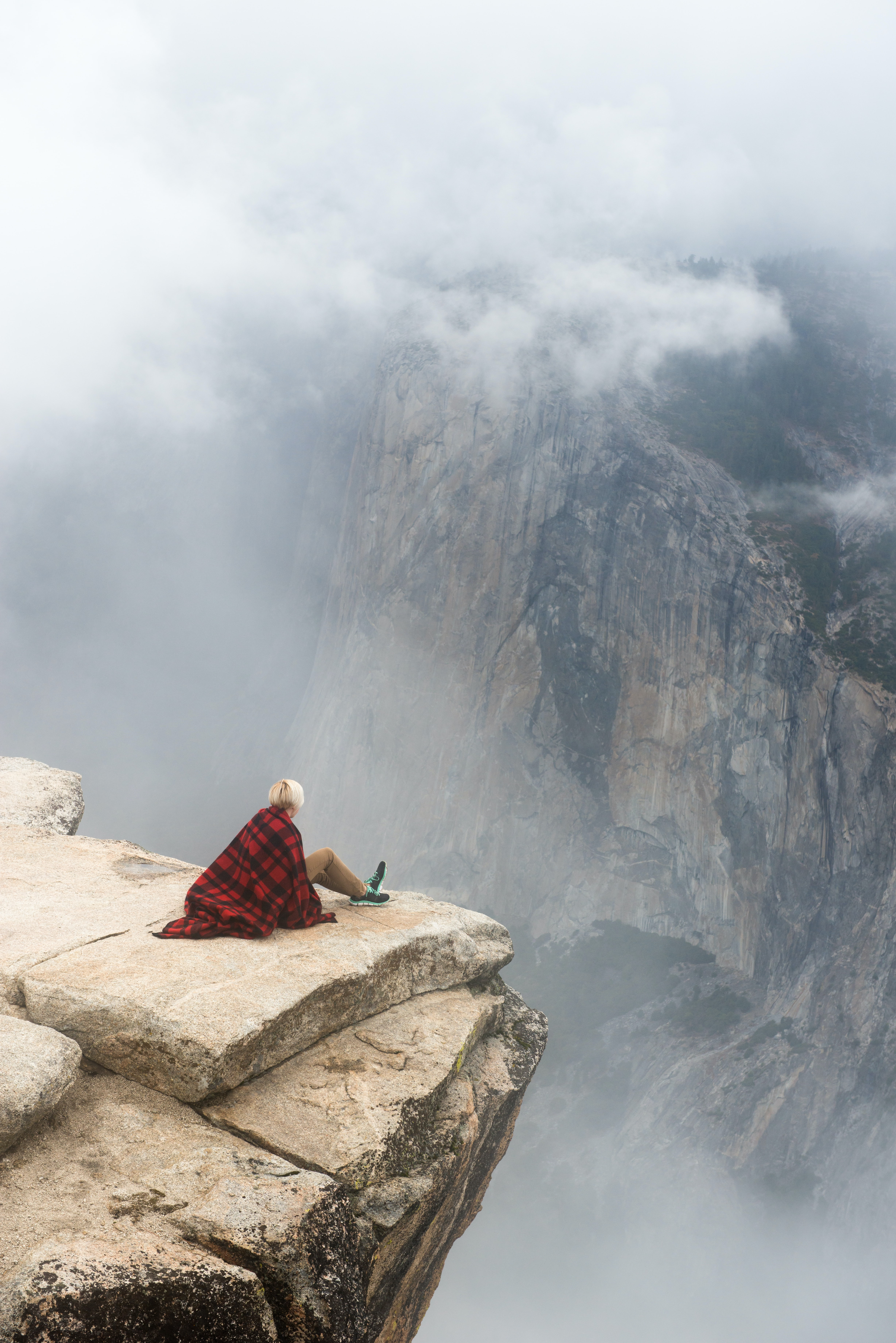 Hiker sits on the rocky ledge of a high mountain in Yosemite National Park