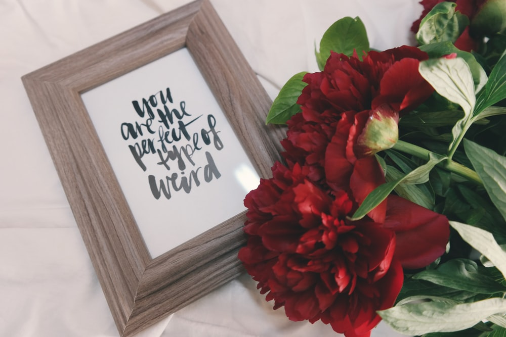"Flowers with framed art that reads ""You are the perfect type of weird."""