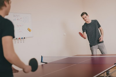 two men playing ping-pong inside room table tennis teams background