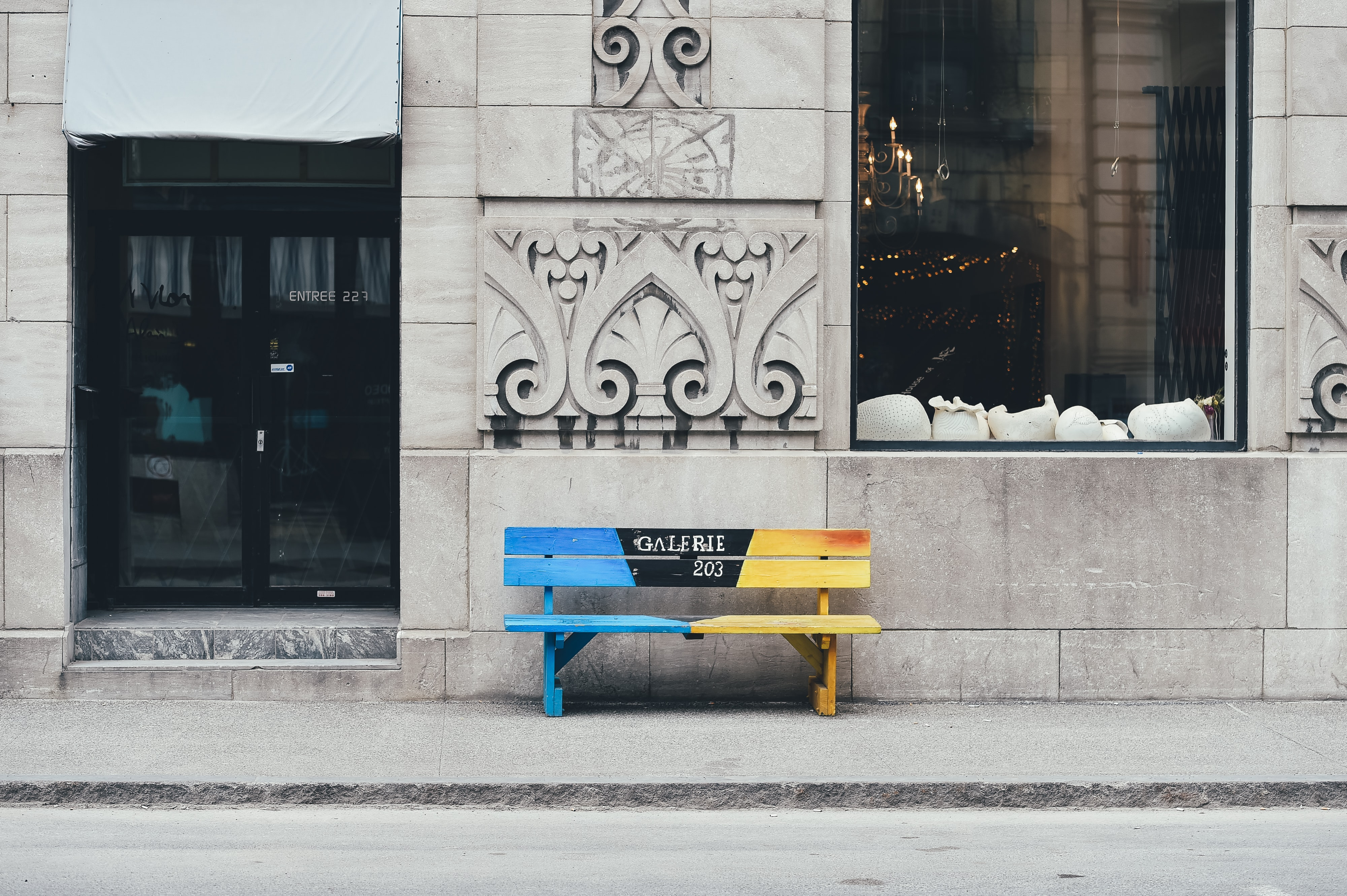 A blue and yellow short wooden bench located on a sidewalk outside a building in old Montreal.