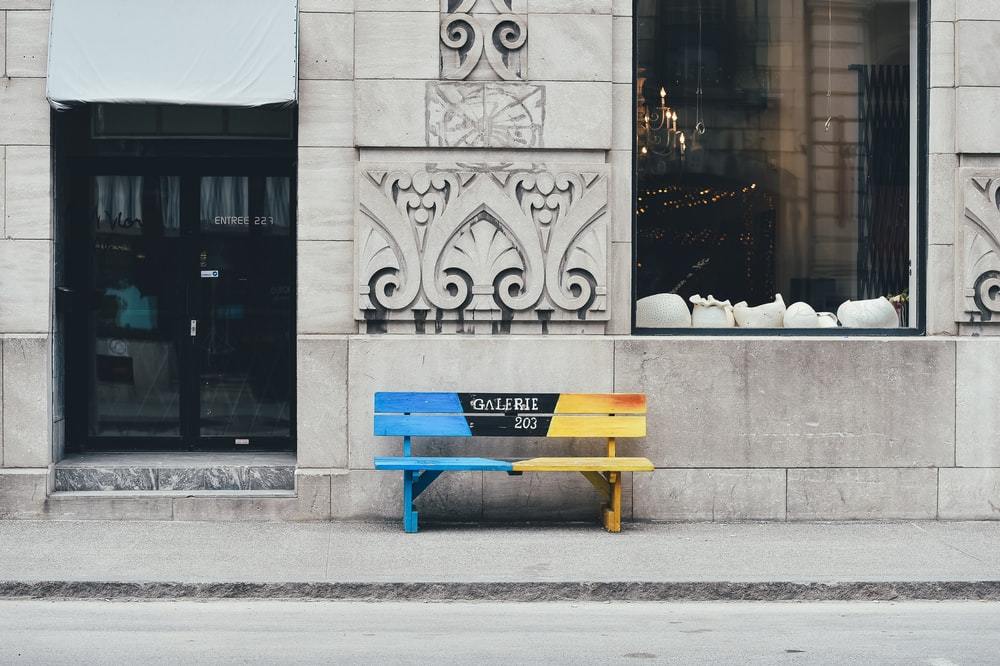 blue and brown wooden bench on sidewalk