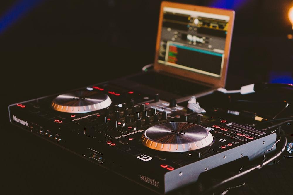 black DJ turn table next to laptop computer