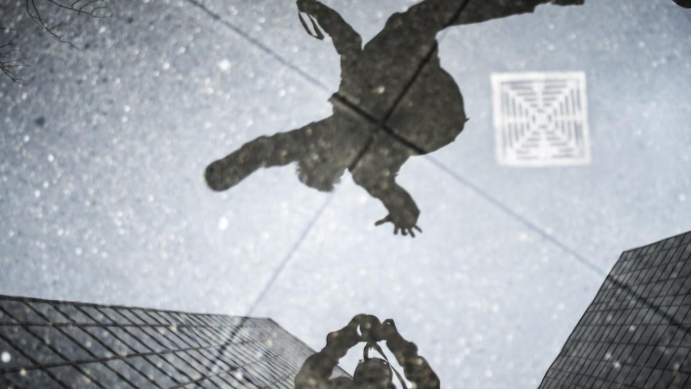 写真家とジャンプする人の水たまりの反射