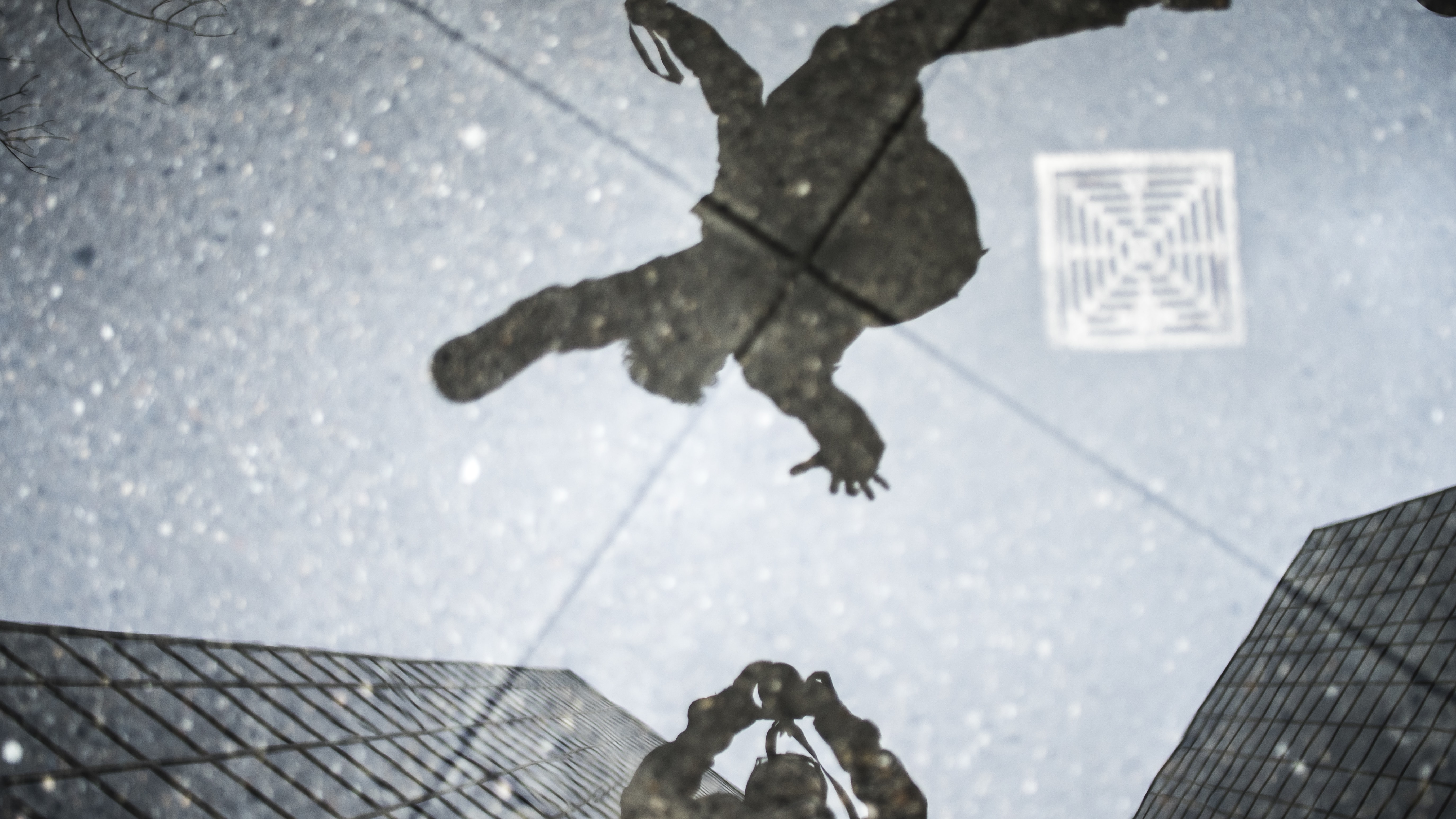 Puddle reflections of a photographer and person jumping