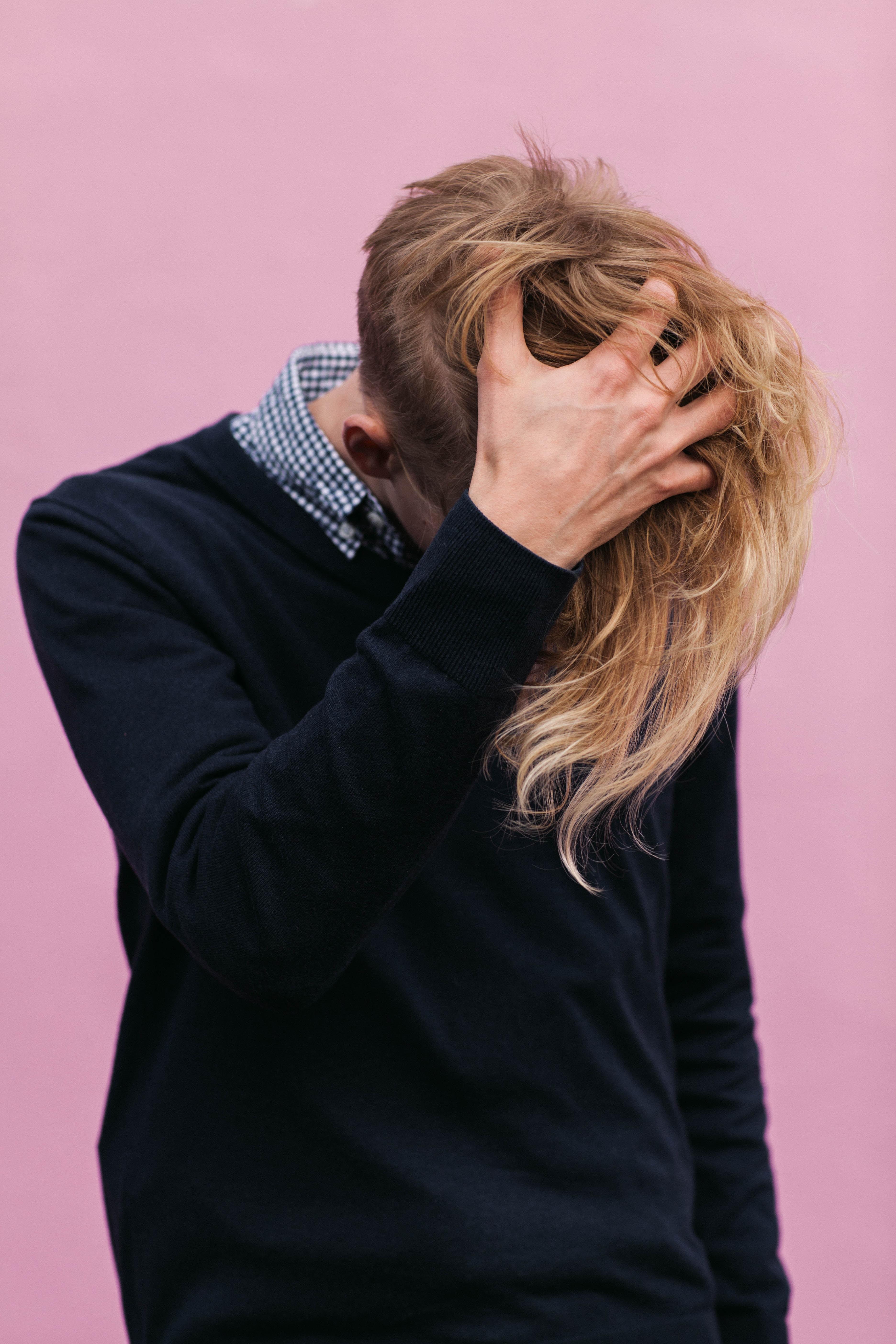 man wearing black crew-neck sweatshirt with hand running through hair