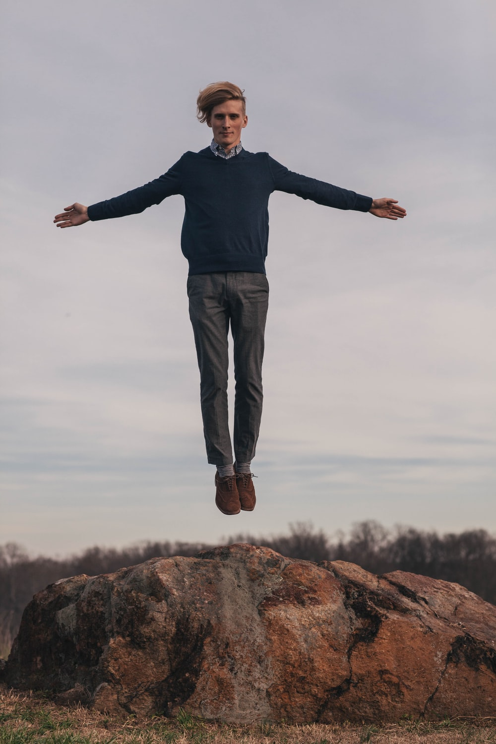 man jumping while open arms